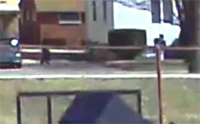 Surveillance footage shows the shooting of Justus Howell. While not readily apparent, authorities say it is at this moment in the footage where Howell turns toward police with a gun in his right hand during a foot chase, prompting officer Eric Hill to fire twice. Hill can be seen at left. Howell can be seen at right between a shrub and a tree.