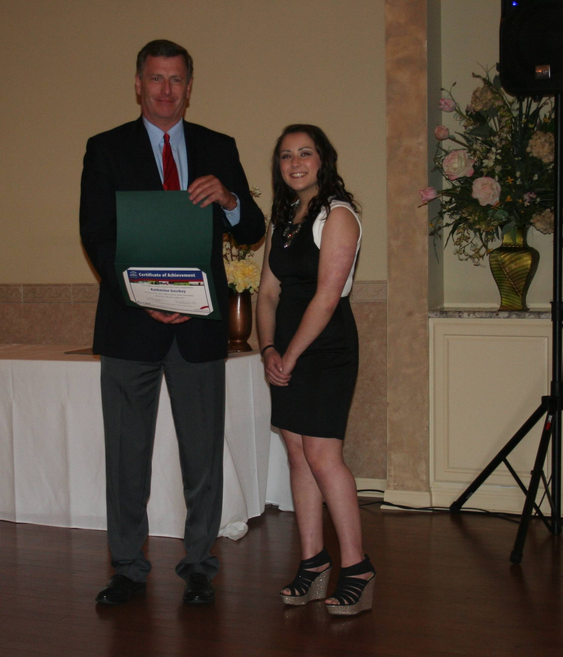 Officer David White presents the 2015 scholarship award toKatherine Goschey at the CAPS dinner, May 14, 2015 Naperville Park District