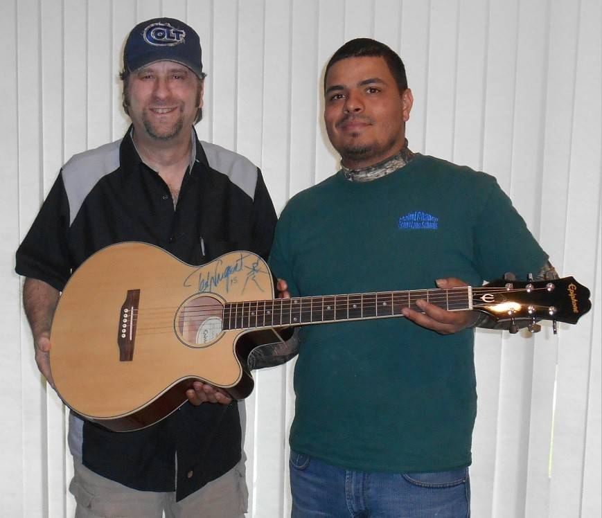Teacher and musician Eric Kinkel, left, shows off a guitar signed by rocker legend Ted Nugent that is presented to Navy veteran Jeremy Renteria.