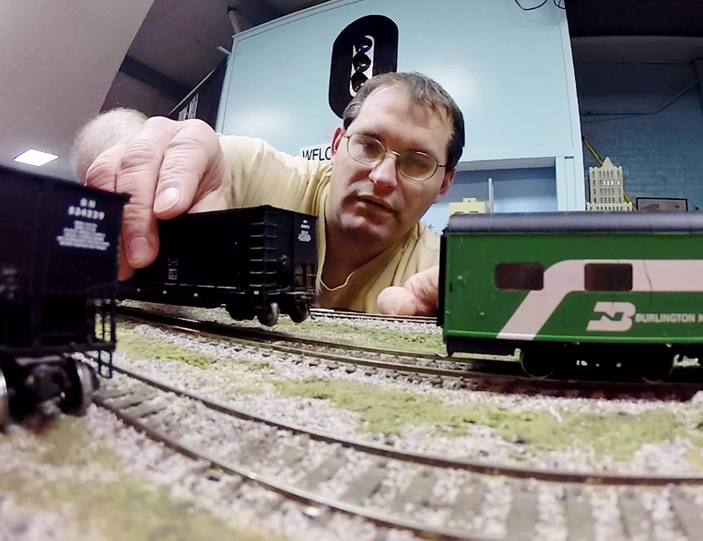 Jim Pechous works above the surface on an HO-scale model train at the Valley Model Railroad Club in South Elgin, but he and club members say you're more likely to find him below the layout, working on the system's complex digital command.