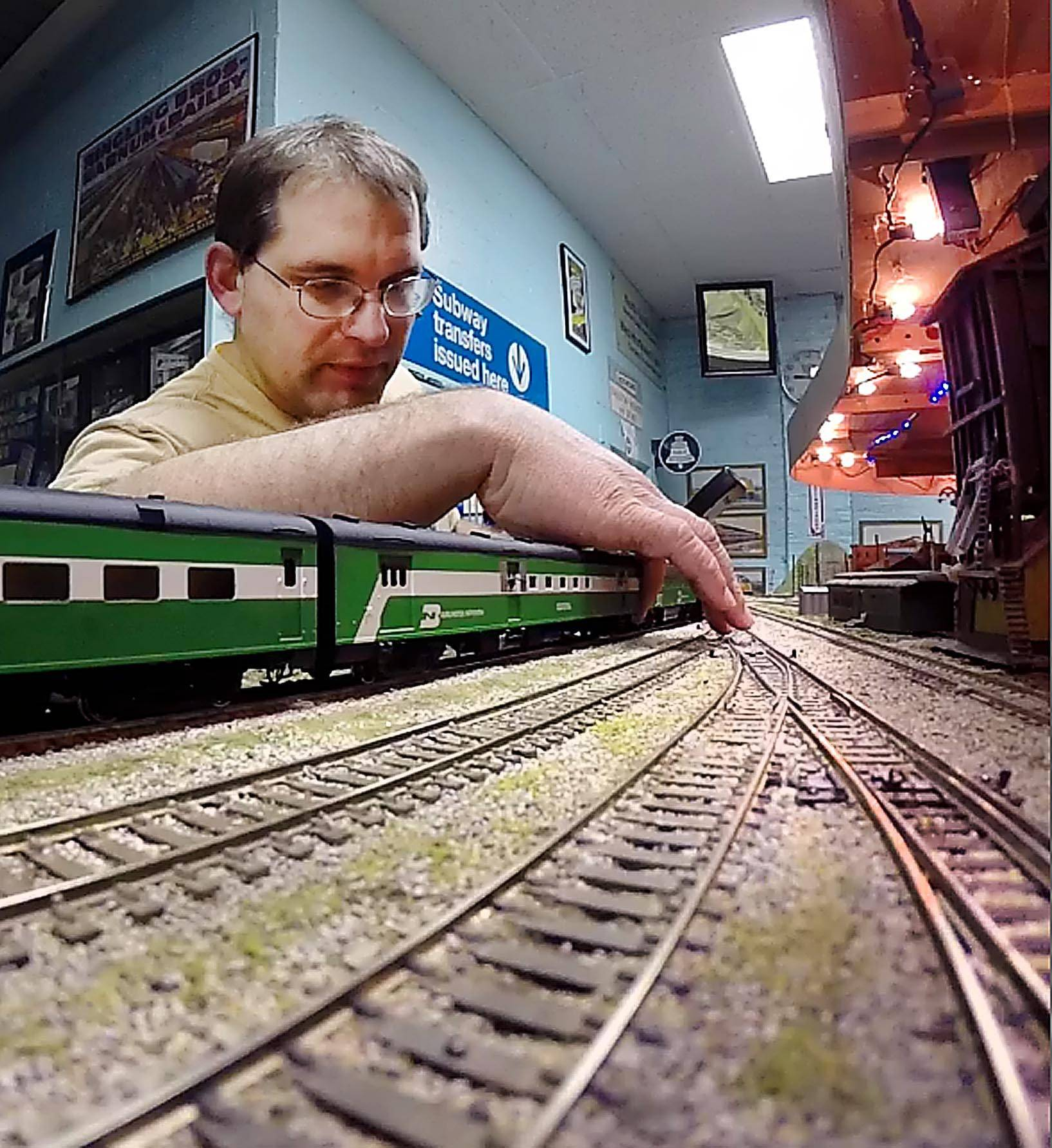 Jim Pechous adjusts his HO scale model train at the Valley Model Railroad Club in South Elgin. Pechous, 31, of Lombard, has a passion for electricity and trains, and combines both as the electrical setup man for the club.
