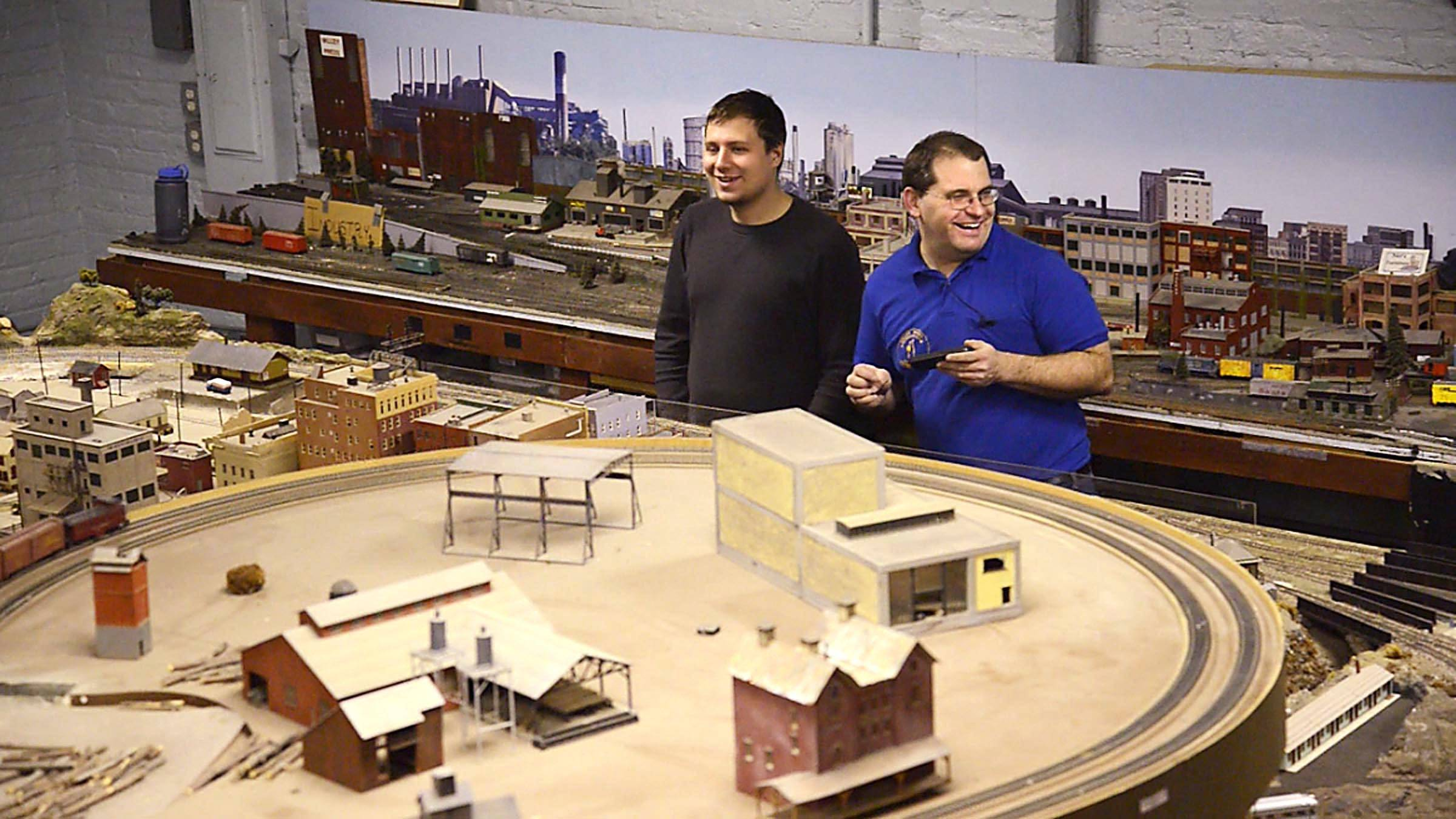 Jim Pechous laughs with club member Trevor Palczynski of Huntley about his ability to wander around the layout and control the track switches with his cellphone.