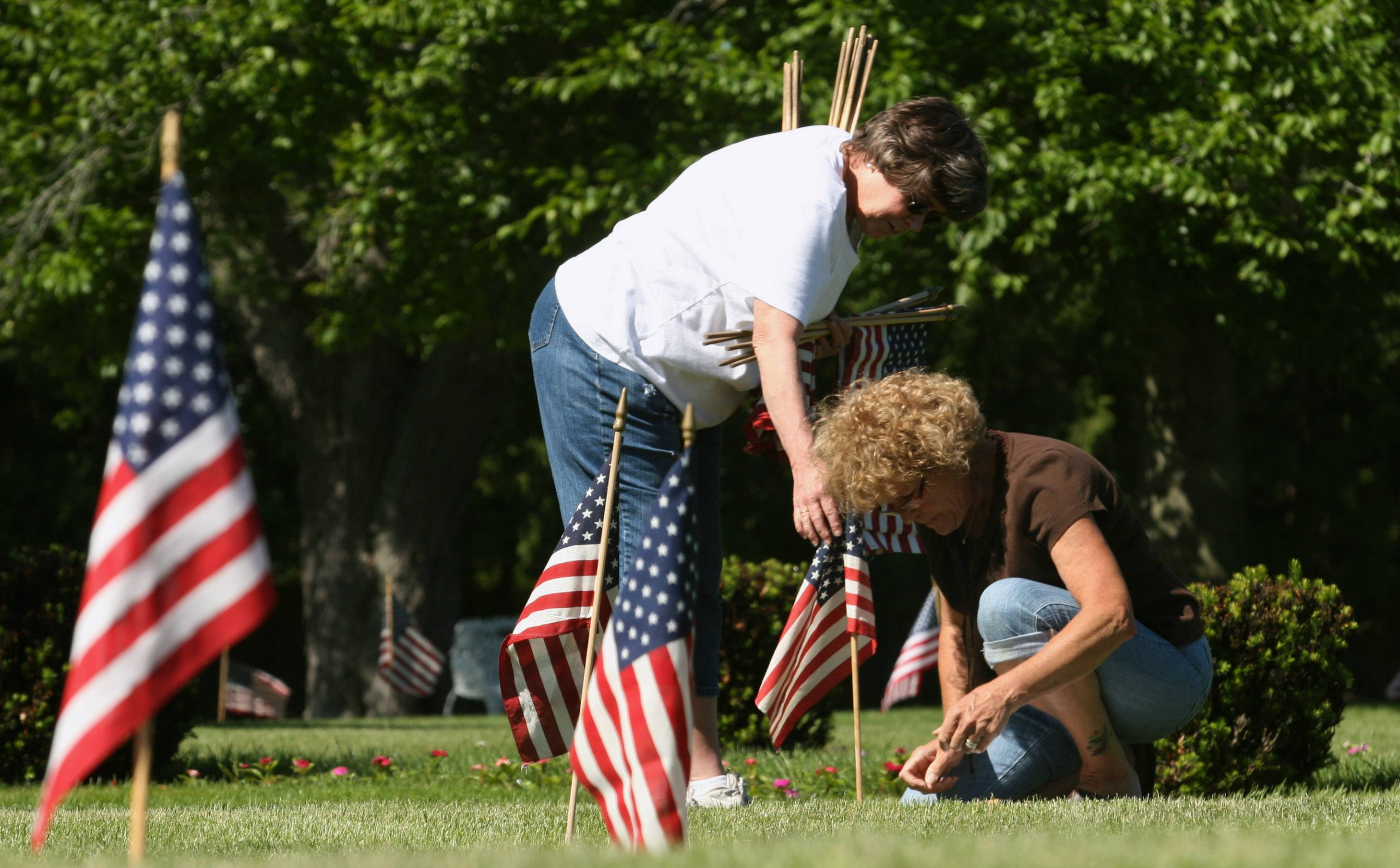 Placing flags on the graves of veterans is a pre-Memorial Day tradition in Dundee Township.