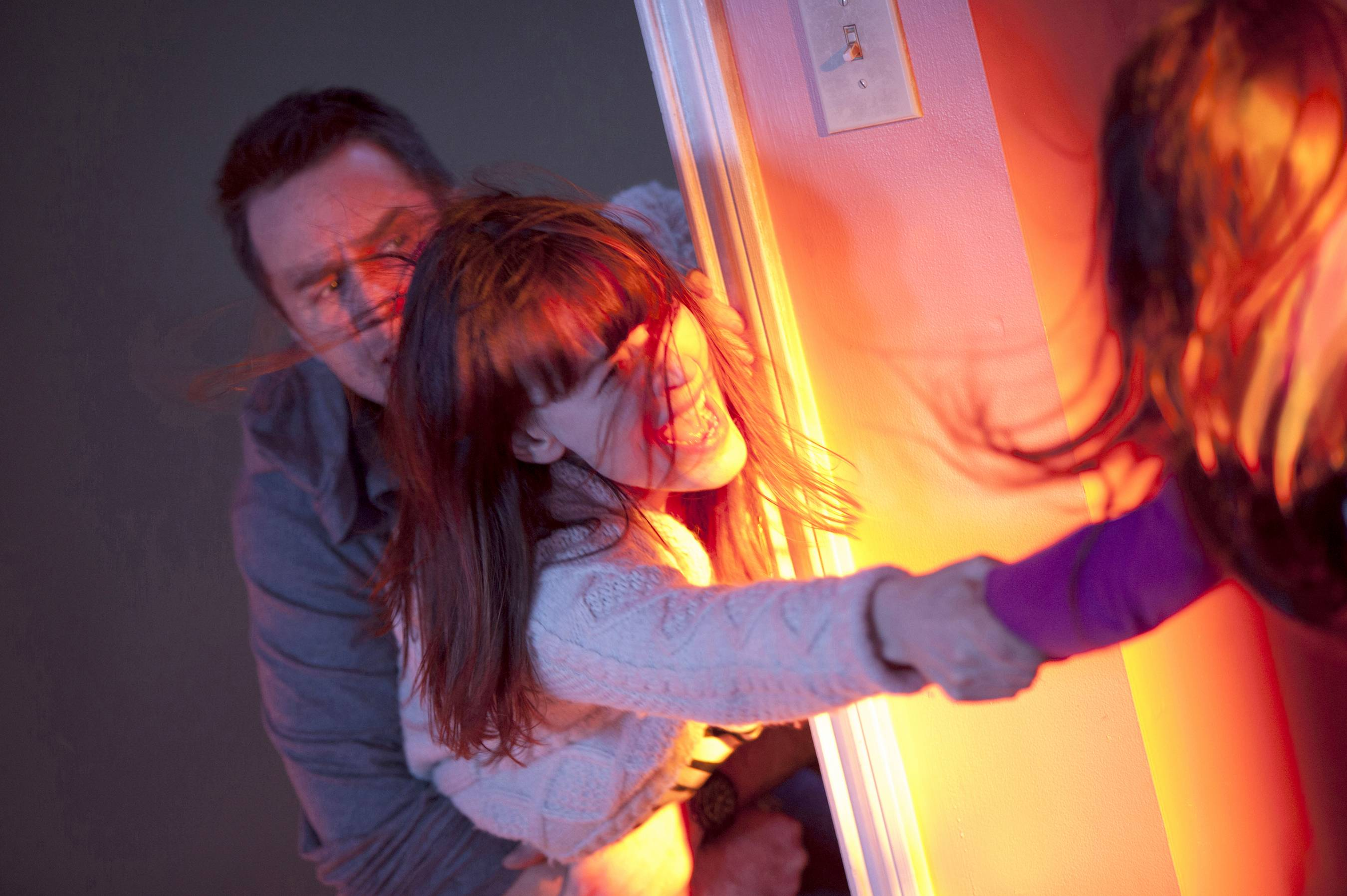"Eric (Sam Rockwell) and Amy (Rosemarie DeWitt) fight to save their daughter, Madison (Kennedi Clements), in ""Poltergeist."""