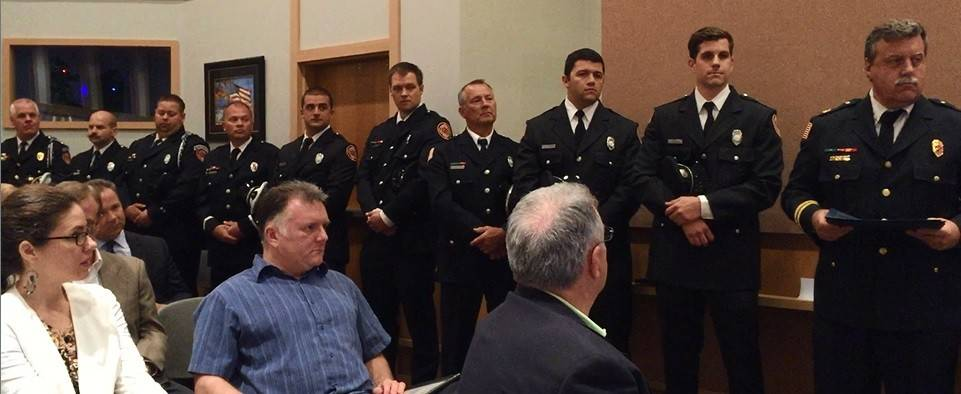 Christopher Browne, middle, who helped save a man who had a heart attack, is in the audience at the Buffalo Grove village board meeting as members of the fire department stand up to be recognized.