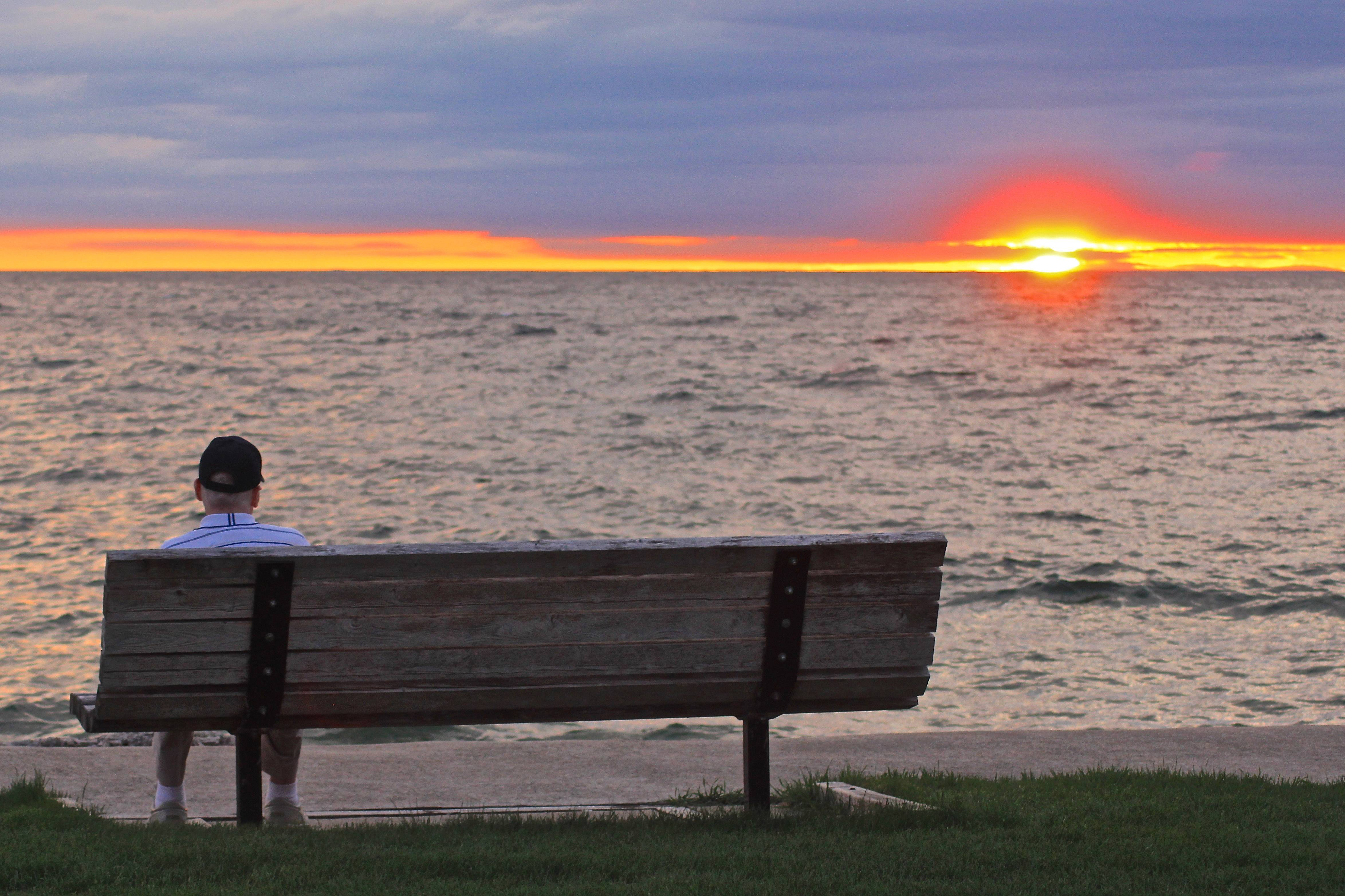 An elderly man sits alone on a bench and enjoys the sunset in Sister Bay, Wisconsin on May 8.