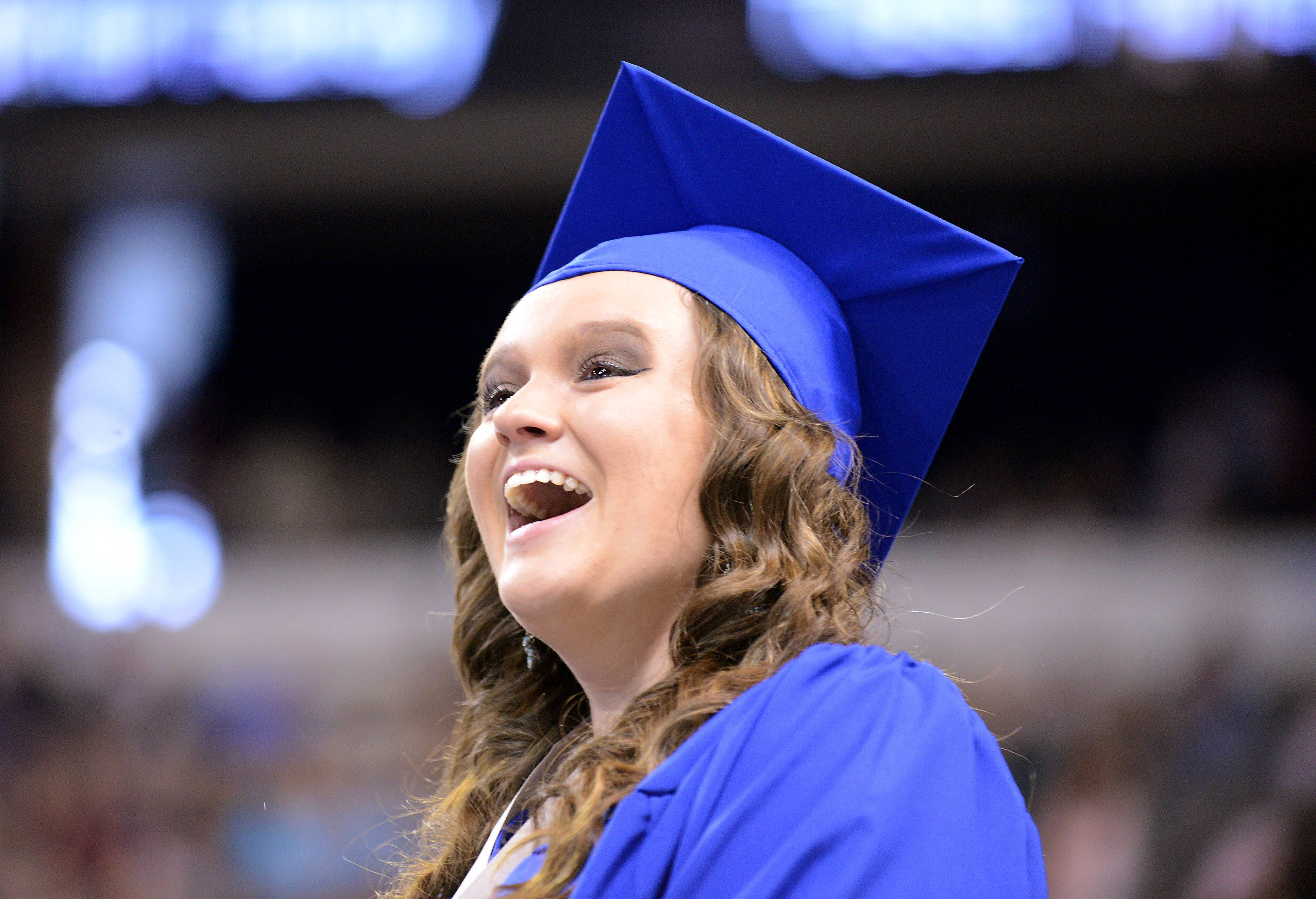 Michelle Cunningham smiles as she spots family in the crowd during the St. Charles North High School graduation ceremony at the Sears Centre in Hoffman Estates Sunday.