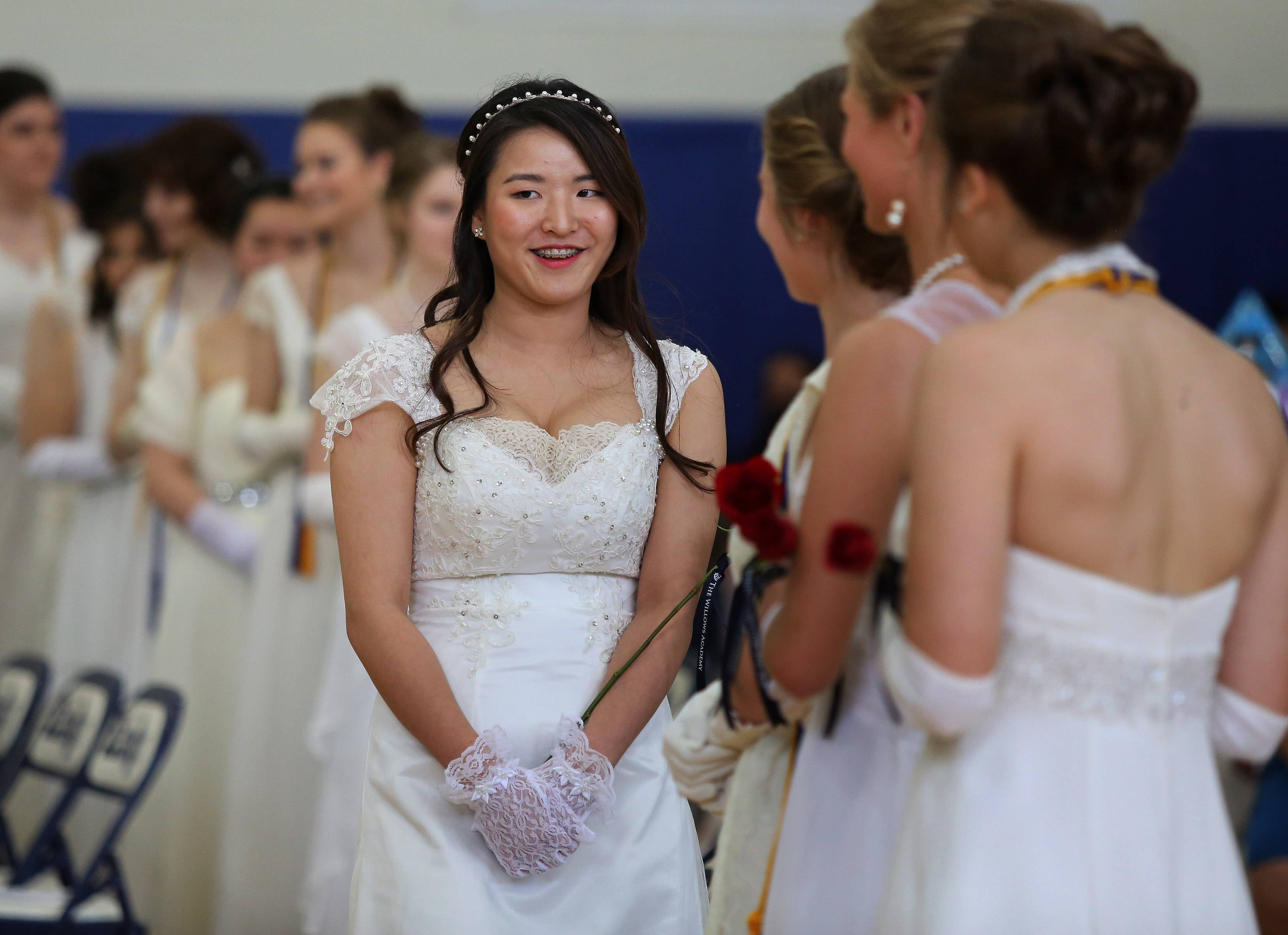 Na Won Park carries a rose as she enters the Willows Academy commencement exercises Sunday at the school. The graduating class consisted of 33 young women.