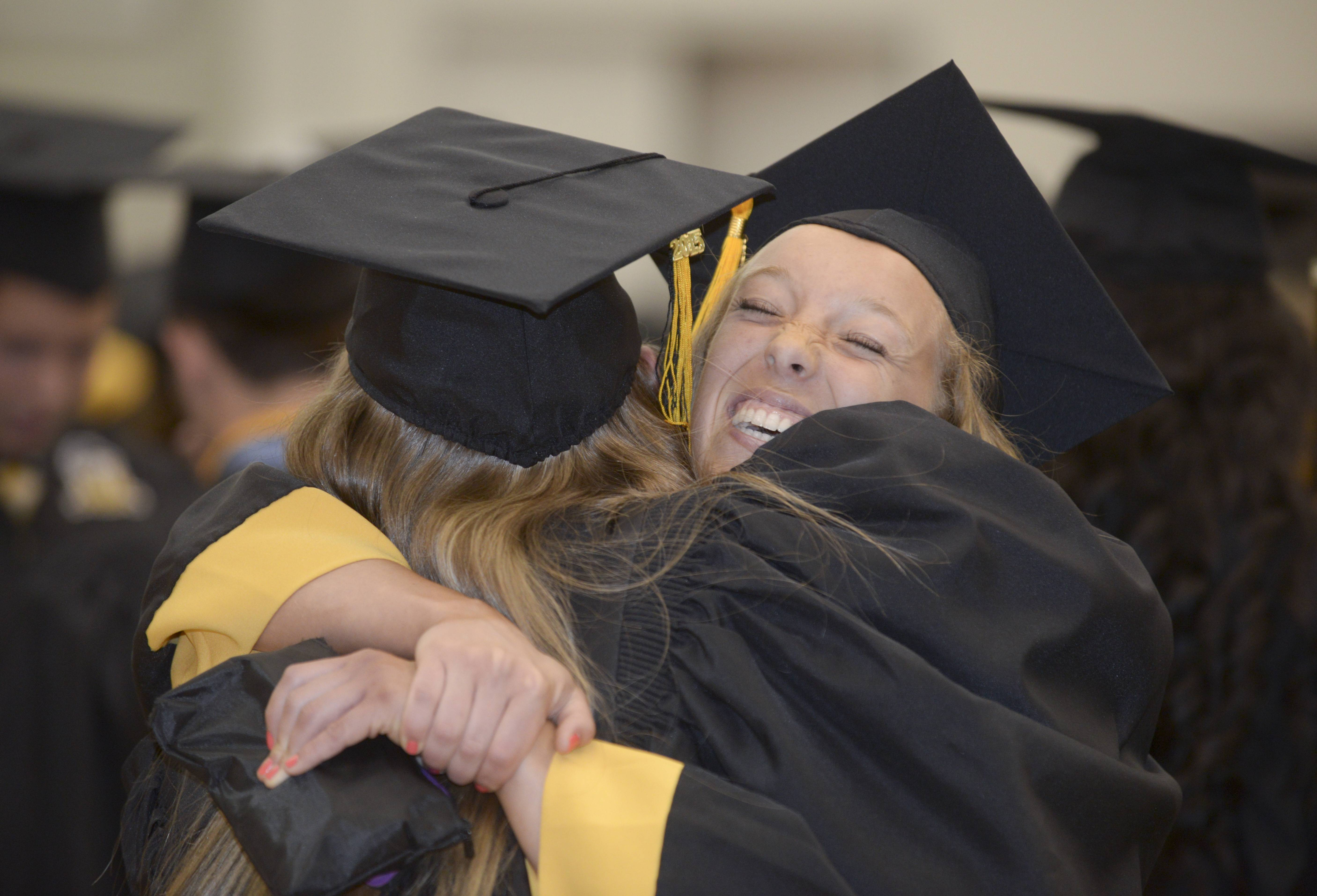 Holly Julifs receives a big hug from Katie E. Kennedy as graduates get ready for the start of the Metea Valley High School graduation on Sunday, May 24 at NIU in DeKalb.