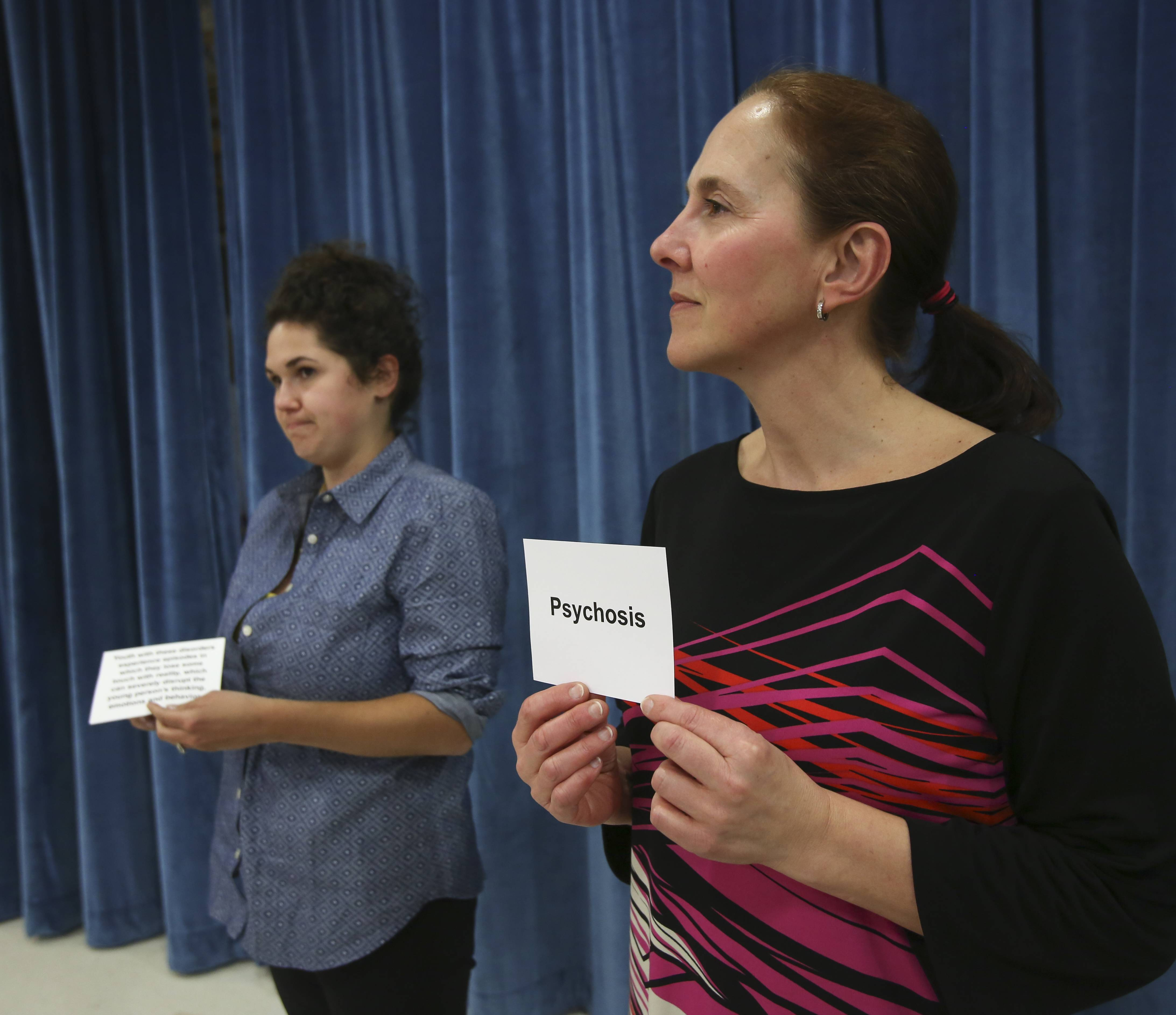 Mental Health First Aid participants Dolores Lago Gonzalez, right, and Brenna Murphy participate in an exercise to identify the likely onset age of different mental health conditions during a recent class in Naperville.