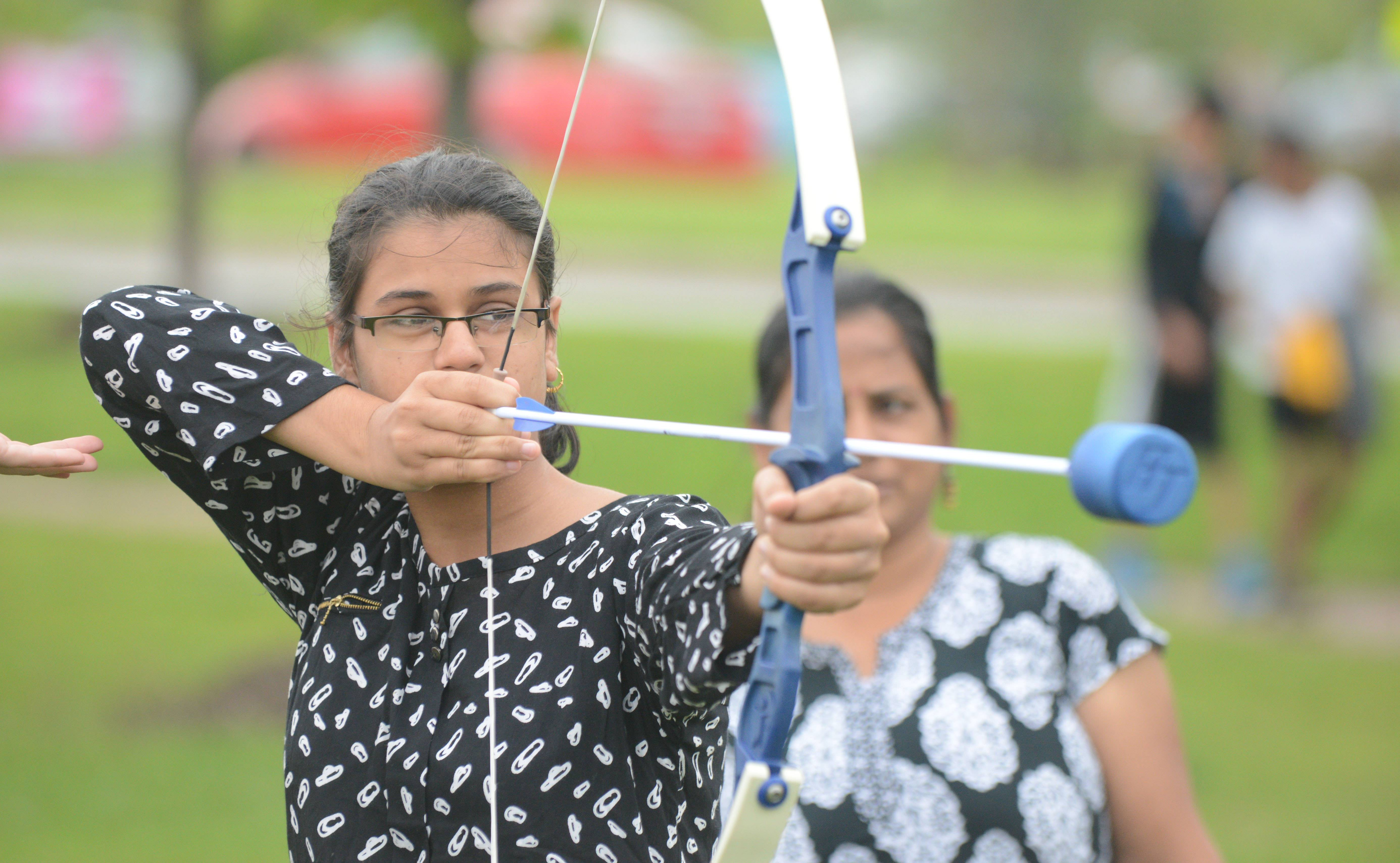 Sonal Chouhan, 18, of Naperville, tries her hand at archery at the JustPlay! Sports and Recreation Festival Saturday in Carol Stream.