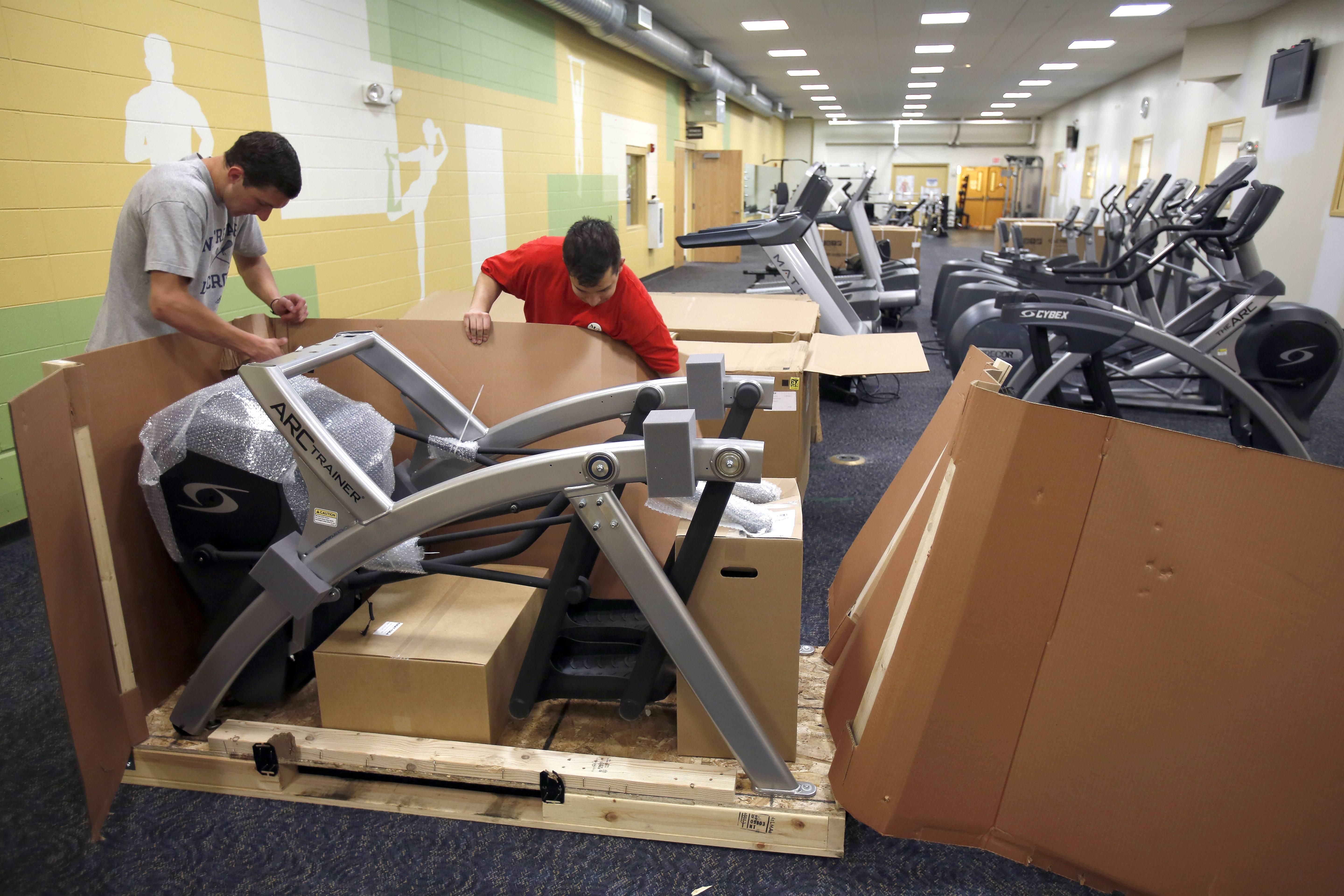 Nick Winter, left, and Evan Bennett, employees of Midwest Commercial Fitness, unpack new disabled-friendly fitness equipment Tuesday at the Huntley Park District Fitness Center. The center, which now has 20 new machines for cardio and strength training, reopens Monday.