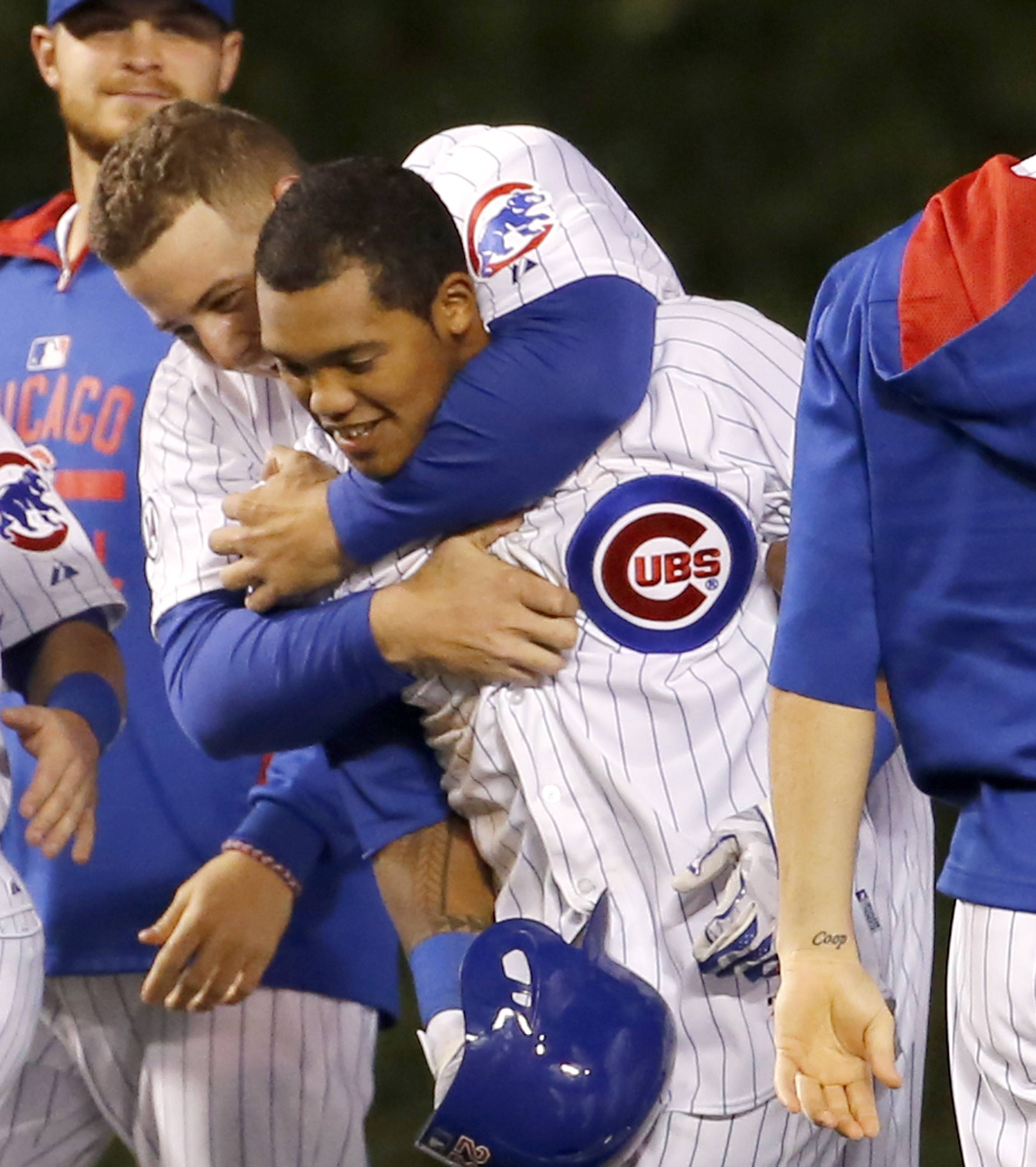 Anthony Rizzo, left, hugs Addison Russell after Russell's game winning double off Washington Nationals relief pitcher Matt Grace during the ninth inning of a baseball game Tuesday, May 26, 2015, in Chicago. Jonathan Herrera scored on the play giving the Cubs a 3-2 win.
