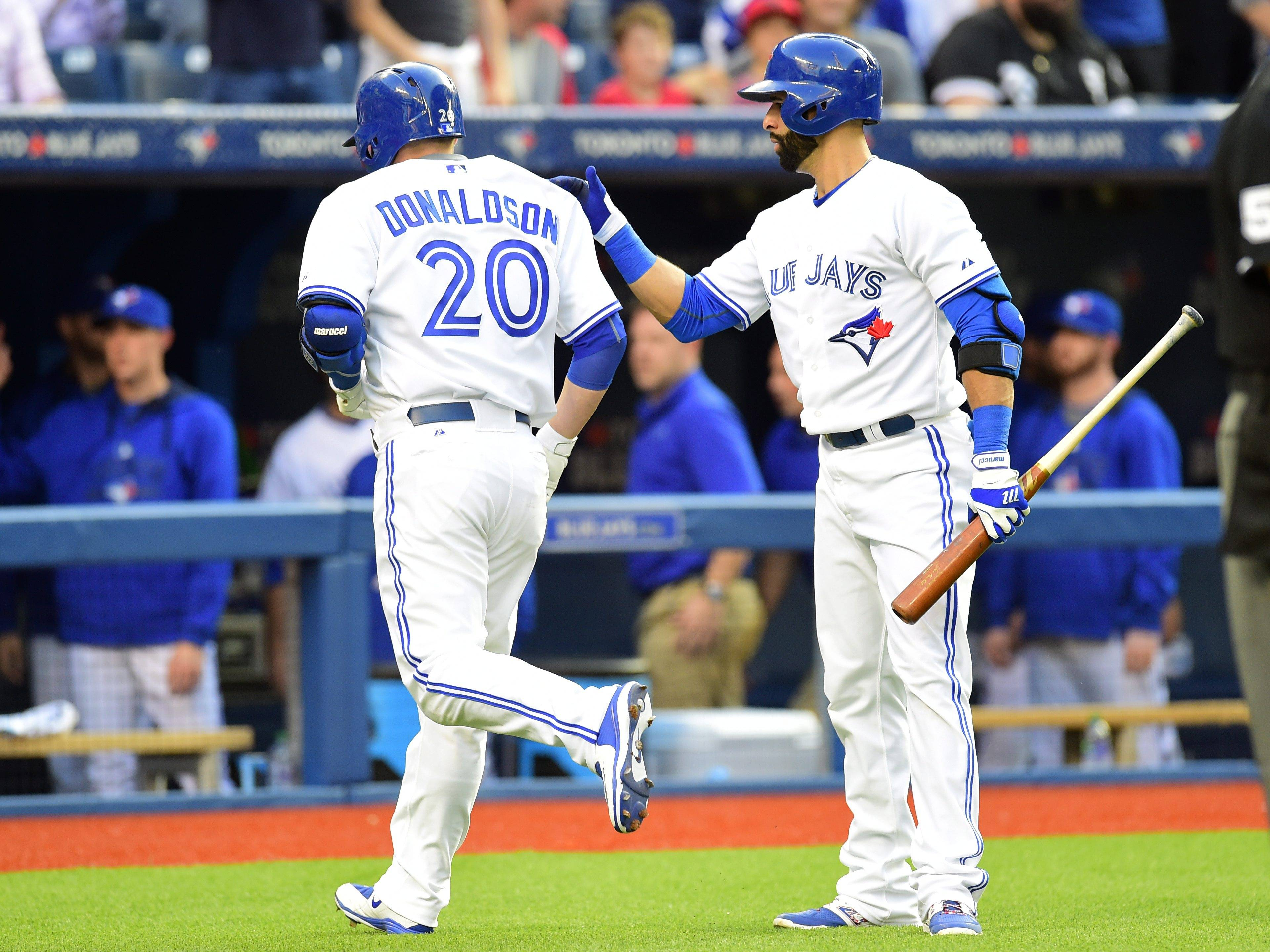 Toronto Blue Jays' Josh Donaldson, left, celebrates with teammate Jose Bautista after hitting a home run during the first inning of American League baseball action against the Chicago White Sox in Toronto on Tuesday, May 26, 2015.