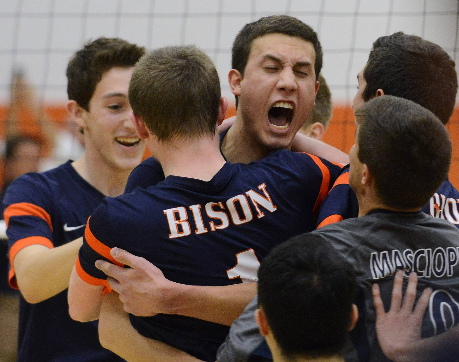 Buffalo Grove's Brendan Ward, left, and Athan Cruz, middle, facing camera, hug teammate Kevin Shanahan, after the Bison defeated Barrington during Wednesday's match.
