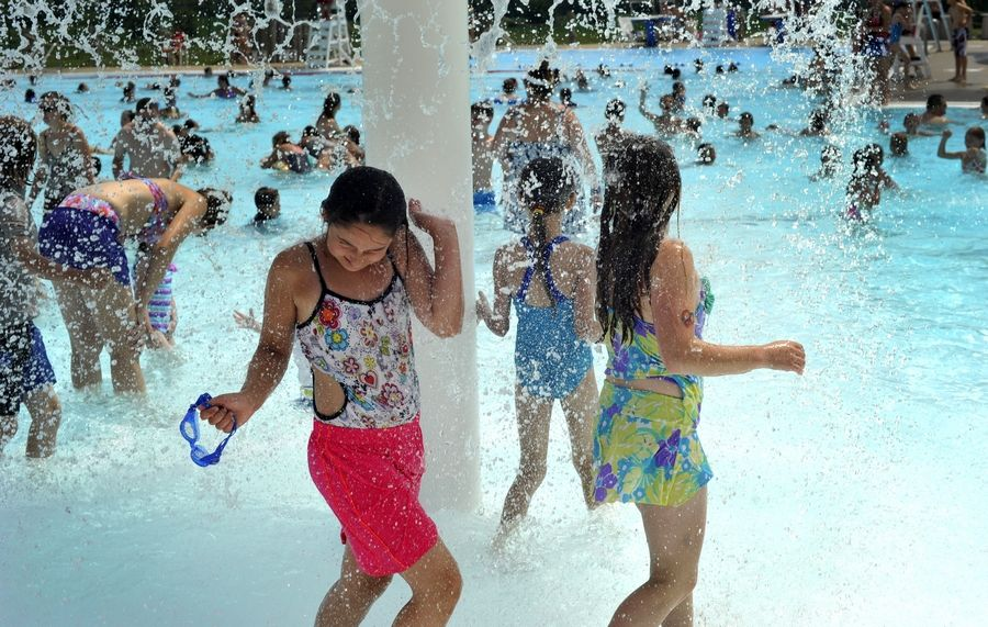 Deidra Toynbee, 10 of Hampshire, left, and Lauren Marckini, 11 of Hampshire, right, have fun playing in the fountain at Stingray Bay water park in Huntley. Like many pools in the Fox Valley, Stingray Bay has opened for the season.
