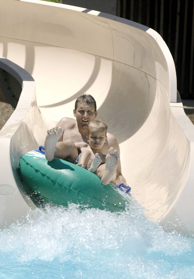 Steve Wit and son, Isaac, 5, of Batavia zip down an inner tube water slide at the Sunset Pool in Geneva. This year, Sunset Pool has added some new features such as an aquatic playground and two climbing walls.