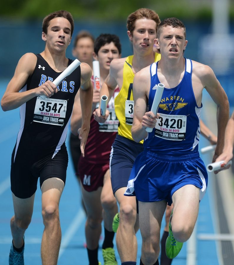 Lake Zurich's Brian Griffith, left, and Warren's Jeff Abbott, middle, carry the batons for their respective teams in the 3,200-meter relay during the Class 3A state meet preliminaries in Charleston on Friday.