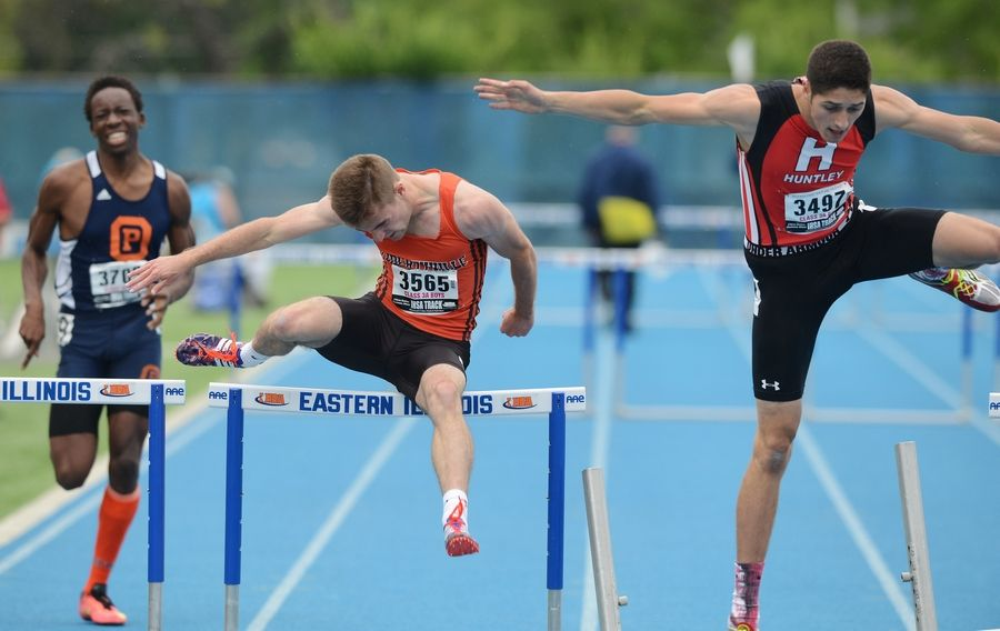 Libertyville's Maxwell Roberts, middle, clears the final hurdle while running adjacent to Huntley's Brennan Bell in the 300-meter intermediate hurdles during the Class 3A state meet preliminaries in Charleston on Friday.