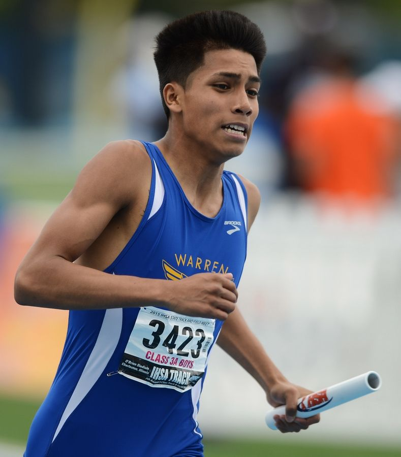 Warren's Hugo Flores carries the baton for his team in the 800-meter relay during the Class 3A state meet preliminaries in Charleston on Friday.