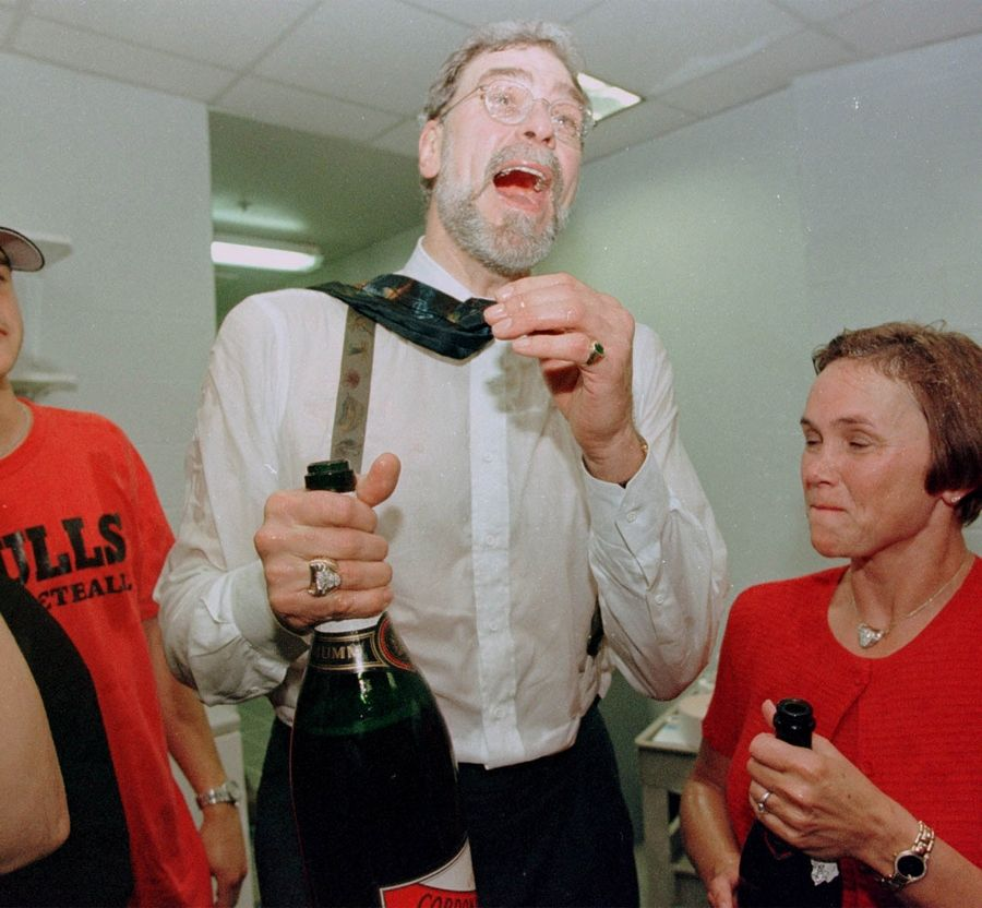 Phil Jackson laughs with a bottle of champagne in his hand in the locker room after the Bulls won game 6 against the Utah Jazz in the NBA Finals for their sixth NBA championship. He also shares something in common with all of Chicago's championship coaches of recent vintage: facial hair.