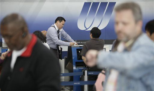 A United gate agent checks passengers in during flight delays at the United Airlines terminal at Chicago's O'Hare International Airport in 2009.