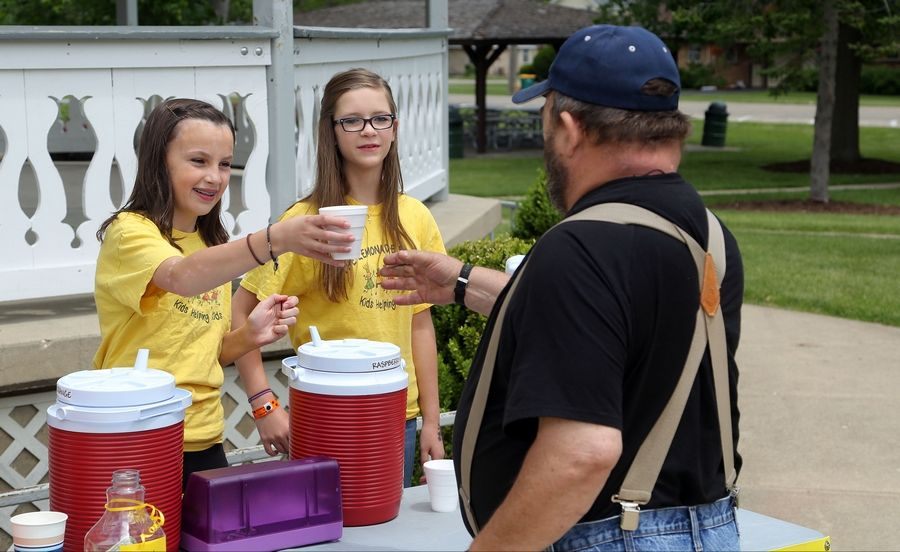 Steve Lundy/slundy@dailyherald.comAubrey Hennig, left, and Samantha Parrish serve lemonade to Ralph Cossiboon of McHenry.