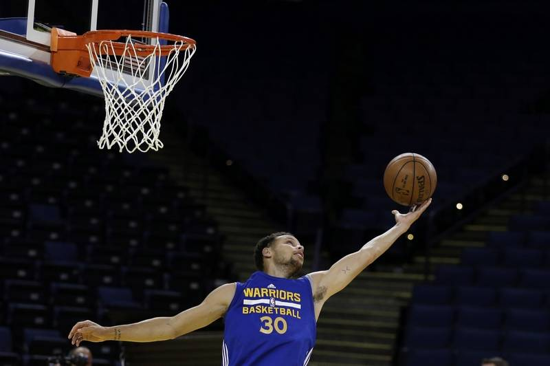 Golden State Warriors' Stephen Curry reaches for the ball during NBA  basketball practice, Wednesday