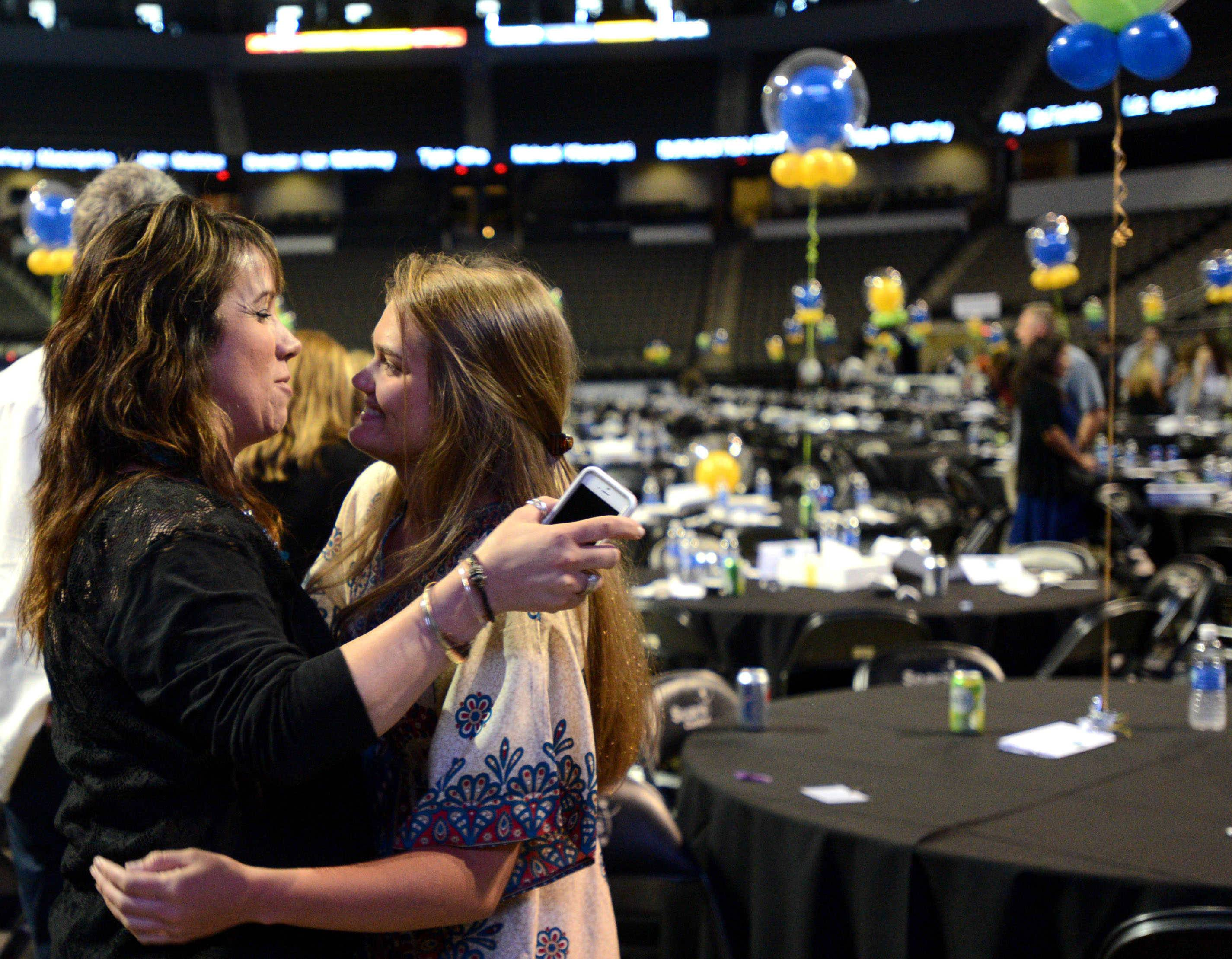 Rolling Meadows' swimming coach Monika Chiapetta, left, congratulates Wheeling's Theresa Godlewski following the Daily Herald Prep Excellence awards banquet Sunday at the Sears Centre Arena in Hoffman Estates.