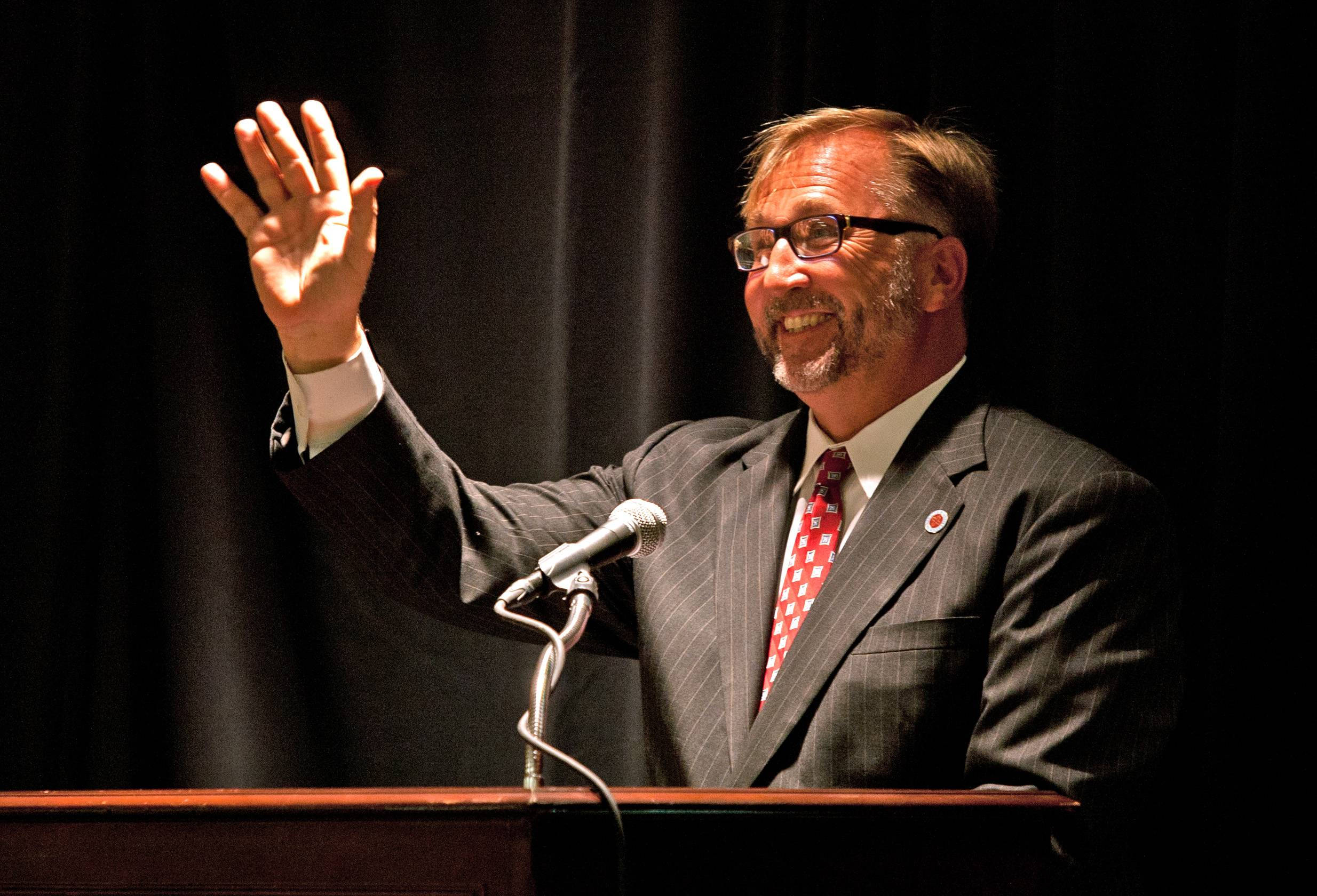 New Benedictine University President Michael S. Brophy waves to a camera Tuesday that was feeding his speech to the university's sites in Asia. Brophy will take over in mid-August from President William Carroll, who is stepping down after 20 years.
