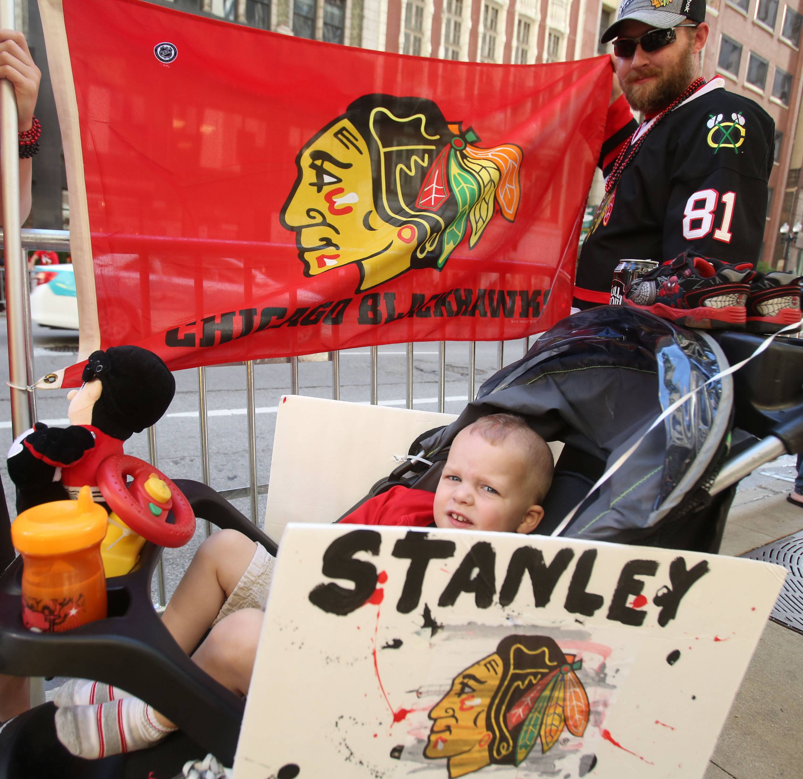 Derek Alford, 3, sits back with his mohawk haircut as his dad Eric Alford, holds a Blackhawks banner. Both of Lake in the Hills, they were waiting for the Stanley Cup parade on Washington Street in Chicago in 2013.