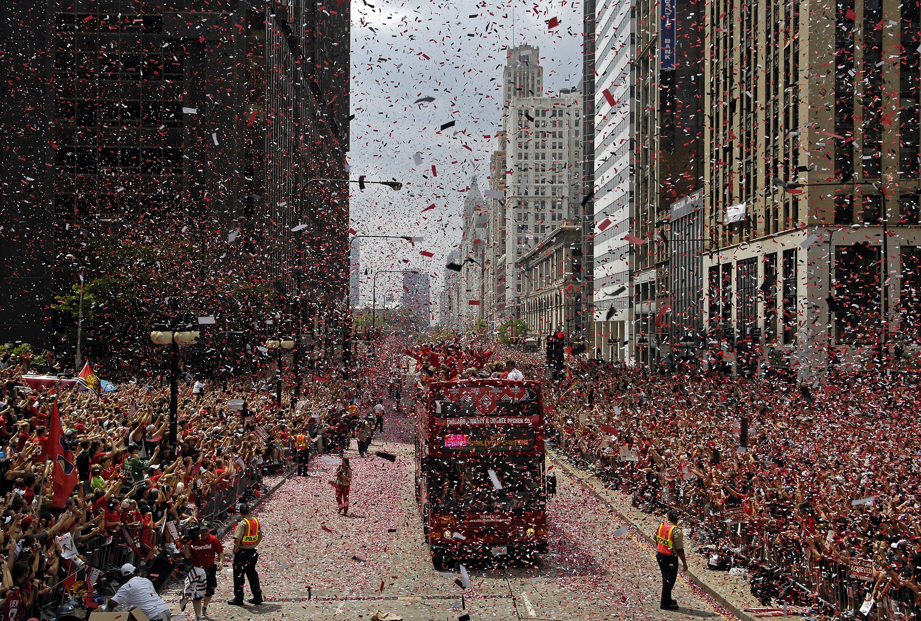 Team buses make their way along Michigan Avenue during the victory parade for the 2013 Chicago Blackhawks following their Stanley Cup victory.