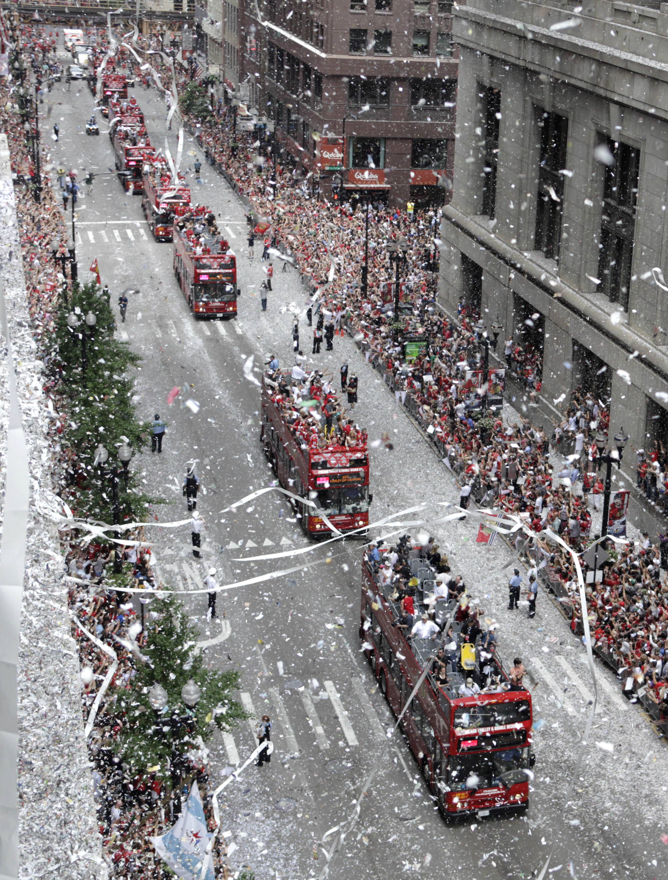 The Chicago Blackhawks ride in double-decker buses with the Stanley Cup during the 2010 ticker tape parade in Chicago.