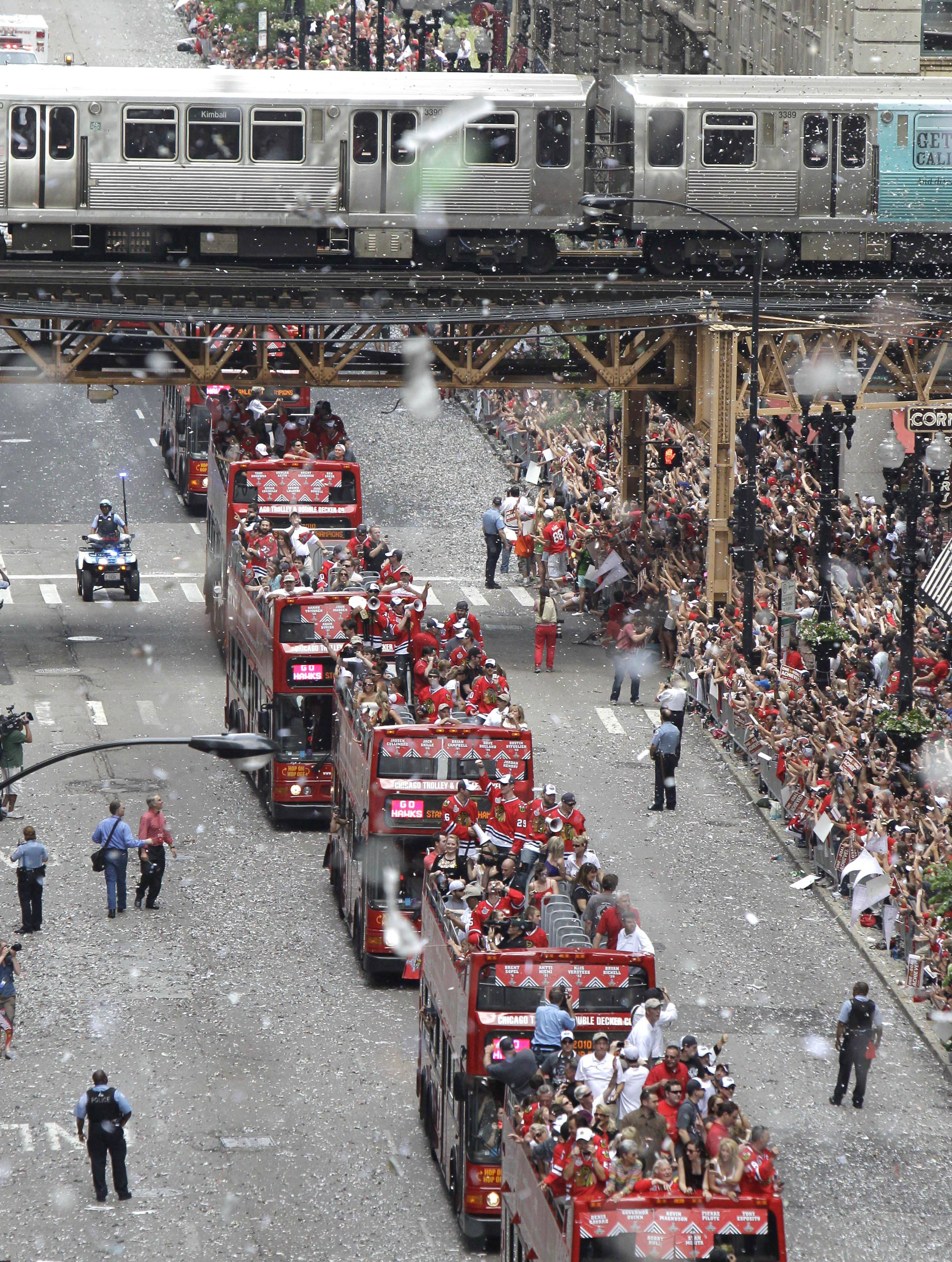 An el train passes over Washington Street as the Chicago Blackhawks ride in double-decker buses with the Stanley Cup during a ticker-tape parade in 2010.
