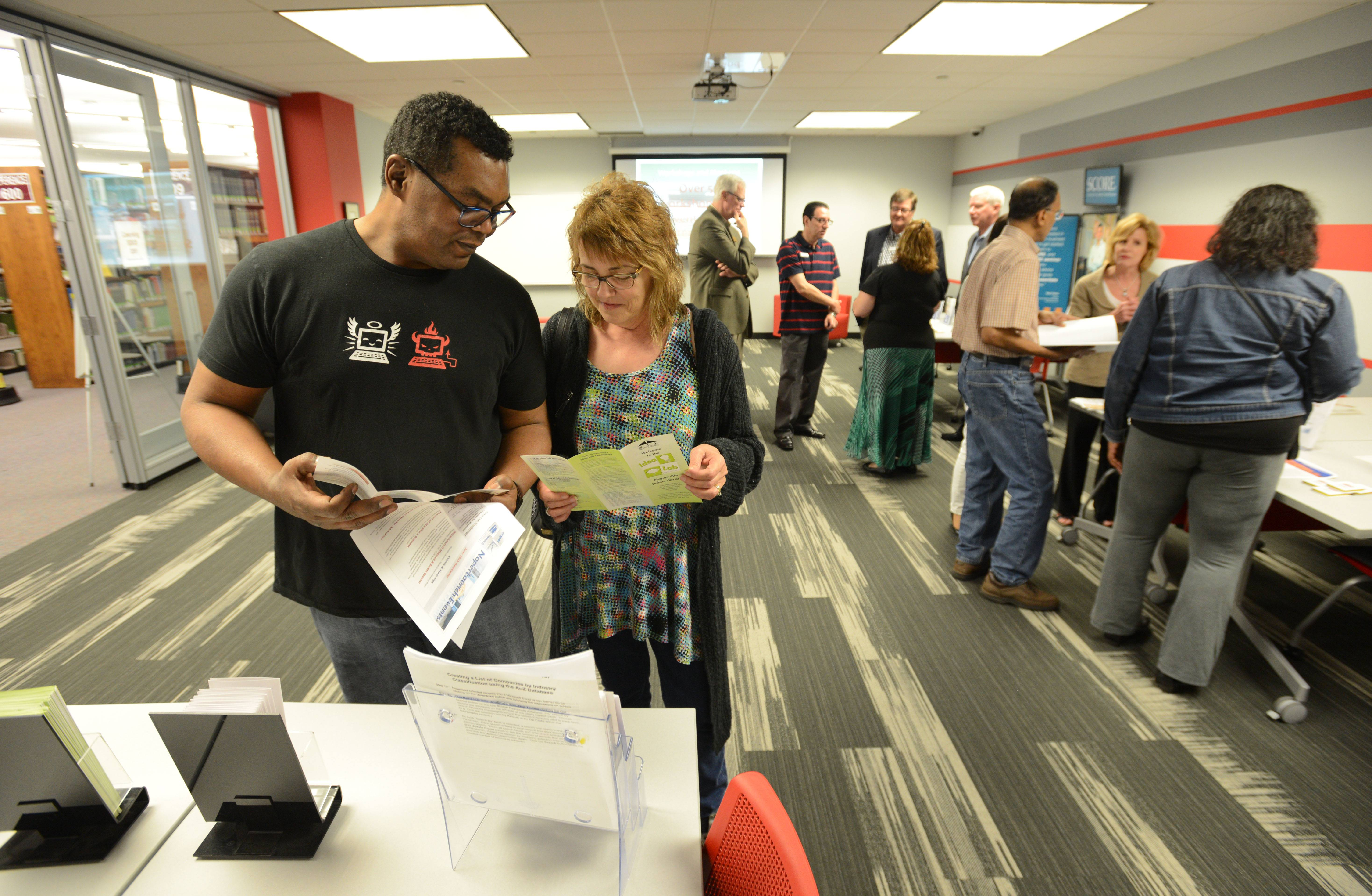 Jose and Janet Osorio of Naperville browse materials at the NaperLaunch business startup center, which hosted a grand opening Wednesday at Nichols Library in downtown Naperville. Janet is contemplating starting a business.