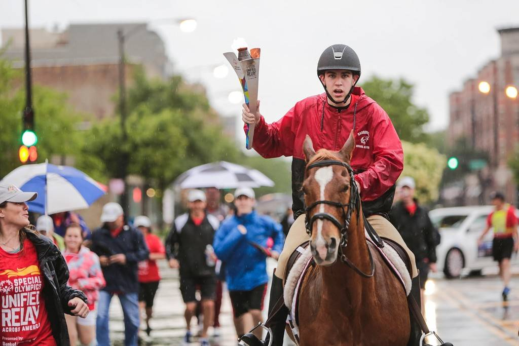 Jake McManus of Lake Barrington carries the Special Olympics torch aboard his beloved horse, Harry, on Saturday through the streets of downtown Chicago.