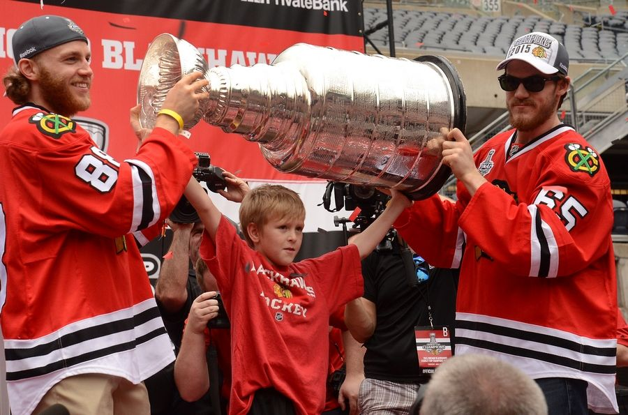 Bob Chwedyk/bchwedyk@dailyherald.comPatrick Kane, left, and Andrew Shaw help C.J. Reif, son of deceased equipment manager Clint Reif, raise the Stanley Cup at the Hawks Rally at Soldier Field.