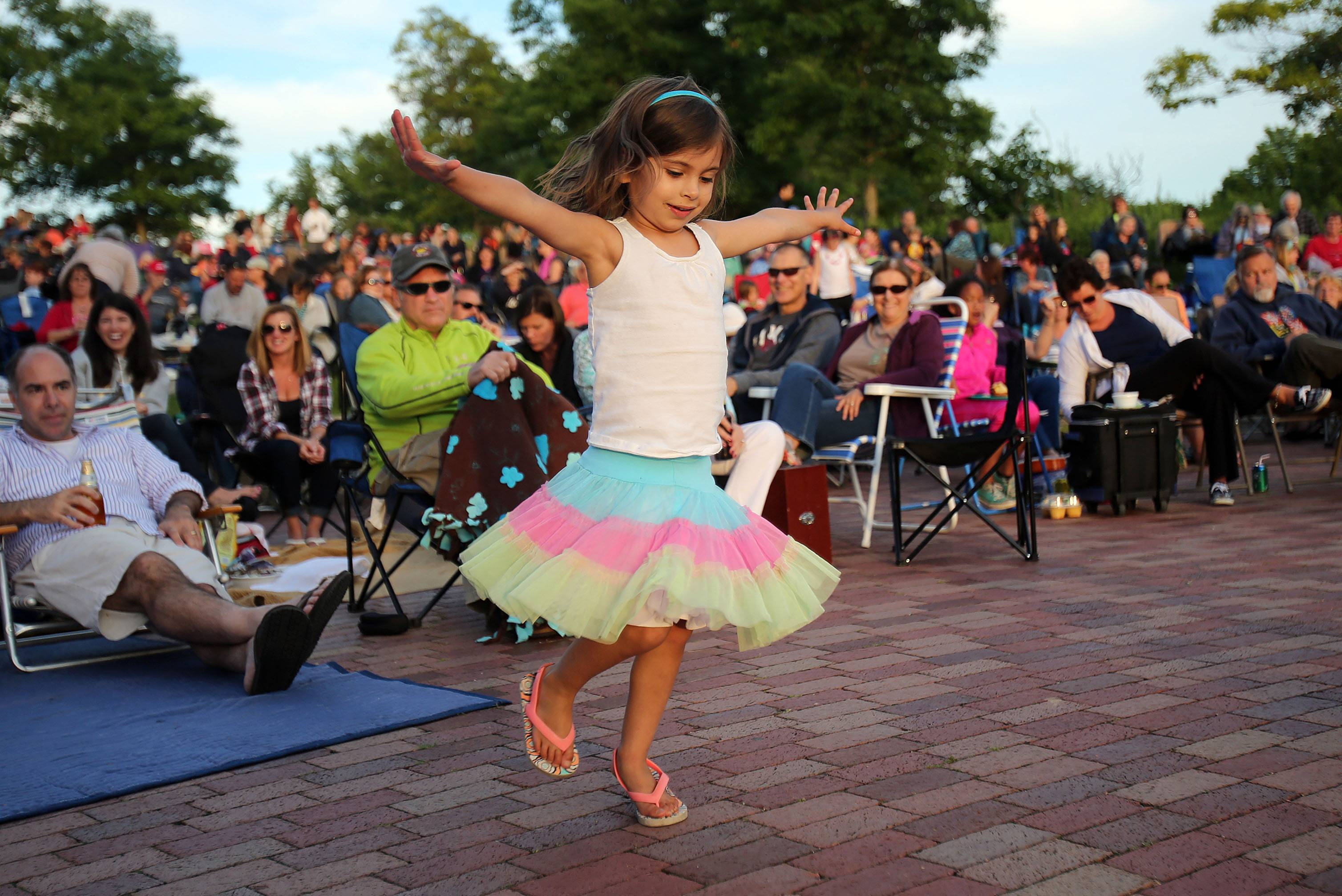 Four-year-old Claire Rehmer, of Libertyville, dances to the American roots musical stylings of the Dang-Its at Independence Grove Forest Preserve as part of its Events in the Plaza series Tuesday in Libertyville.