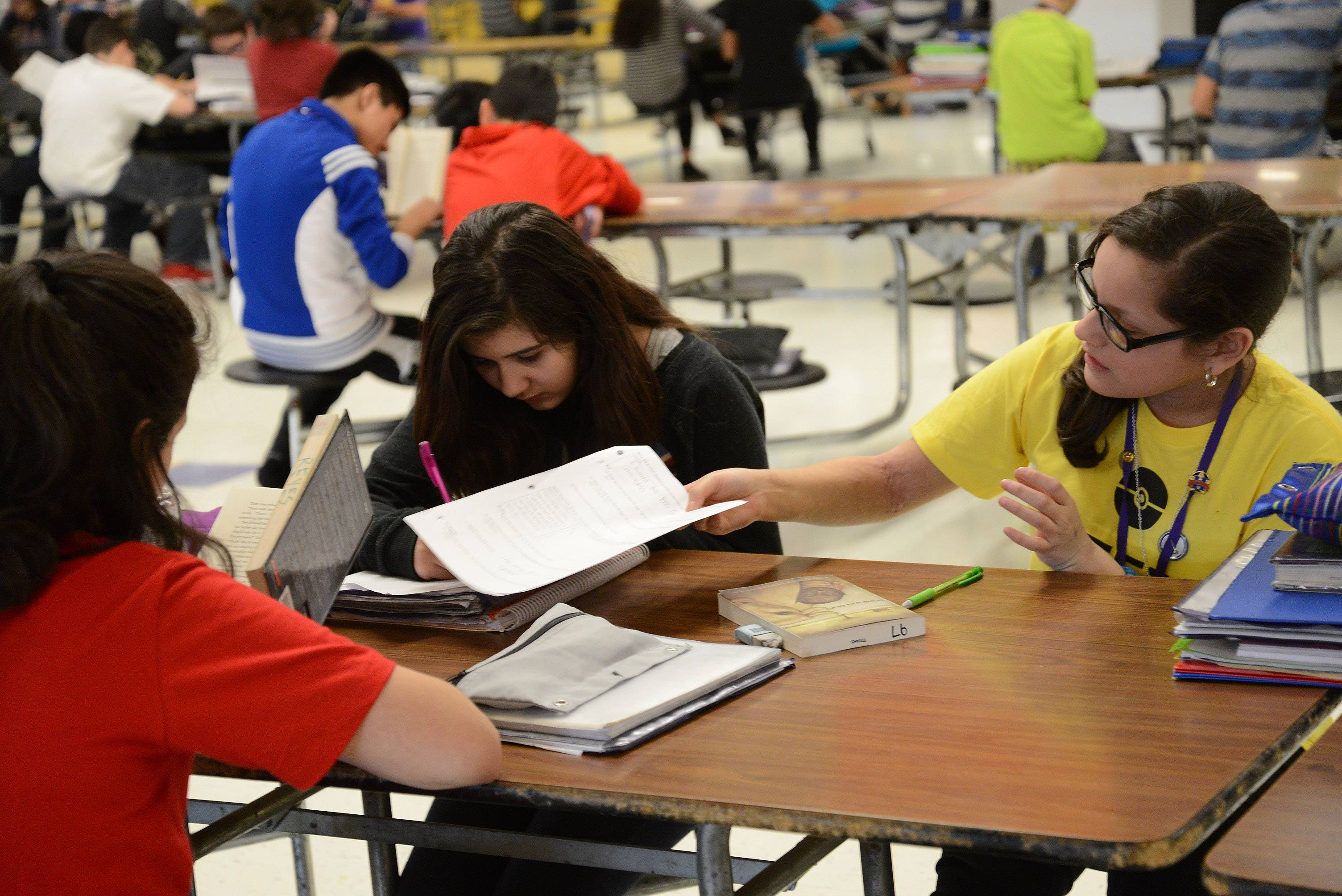 From left, Kaylee Bautista, Shyla Rajabali and Emily Bautista use some quiet time to study before lunch at Tefft Middle School in Streamwood, where nearly 75 percent of students were considered low-income in 2014.