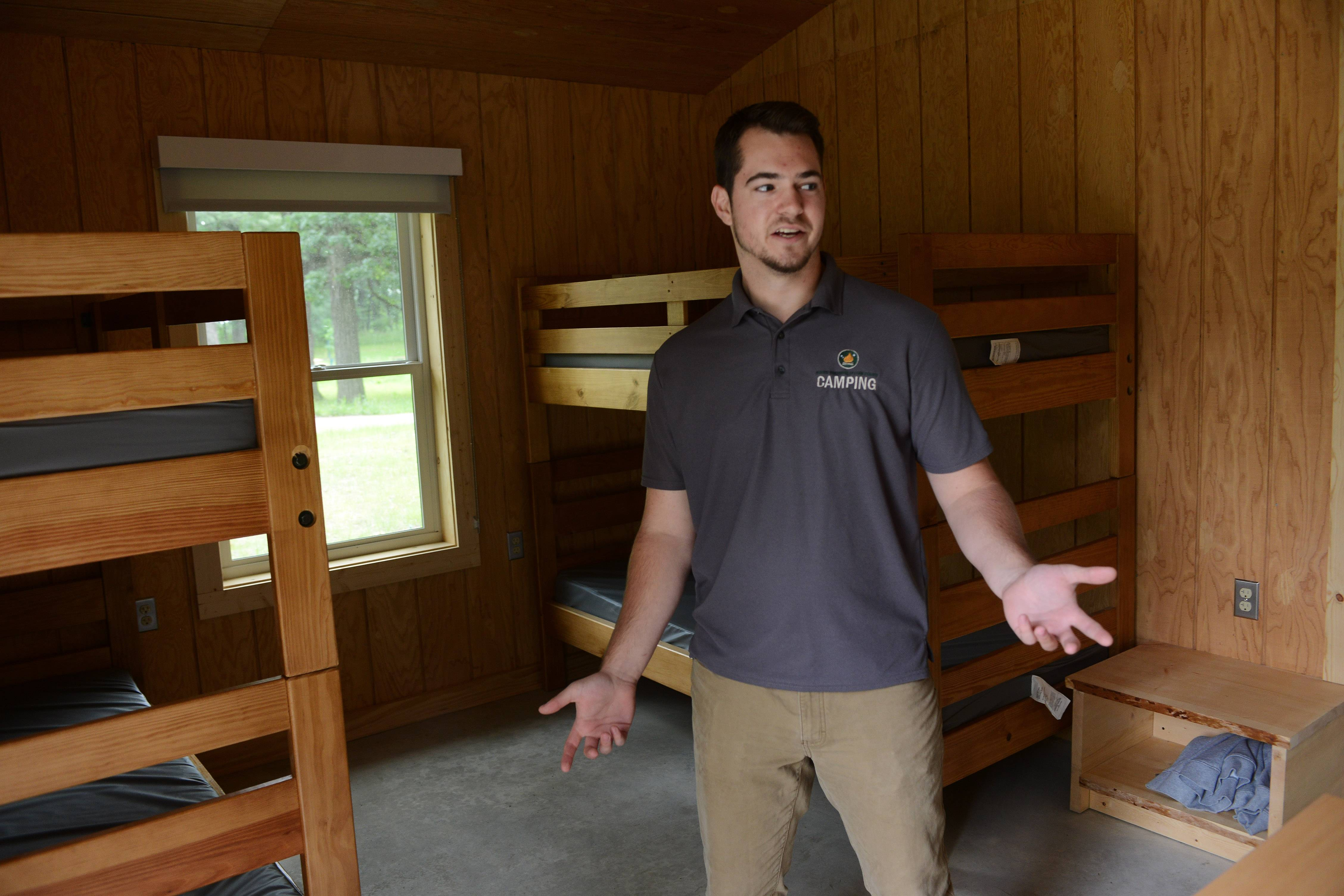 Matthew Brandt, assistant general manager at Camp Reinberg, shows the interior of a 10-person cabin at the new facility, which opens today near Palatine.