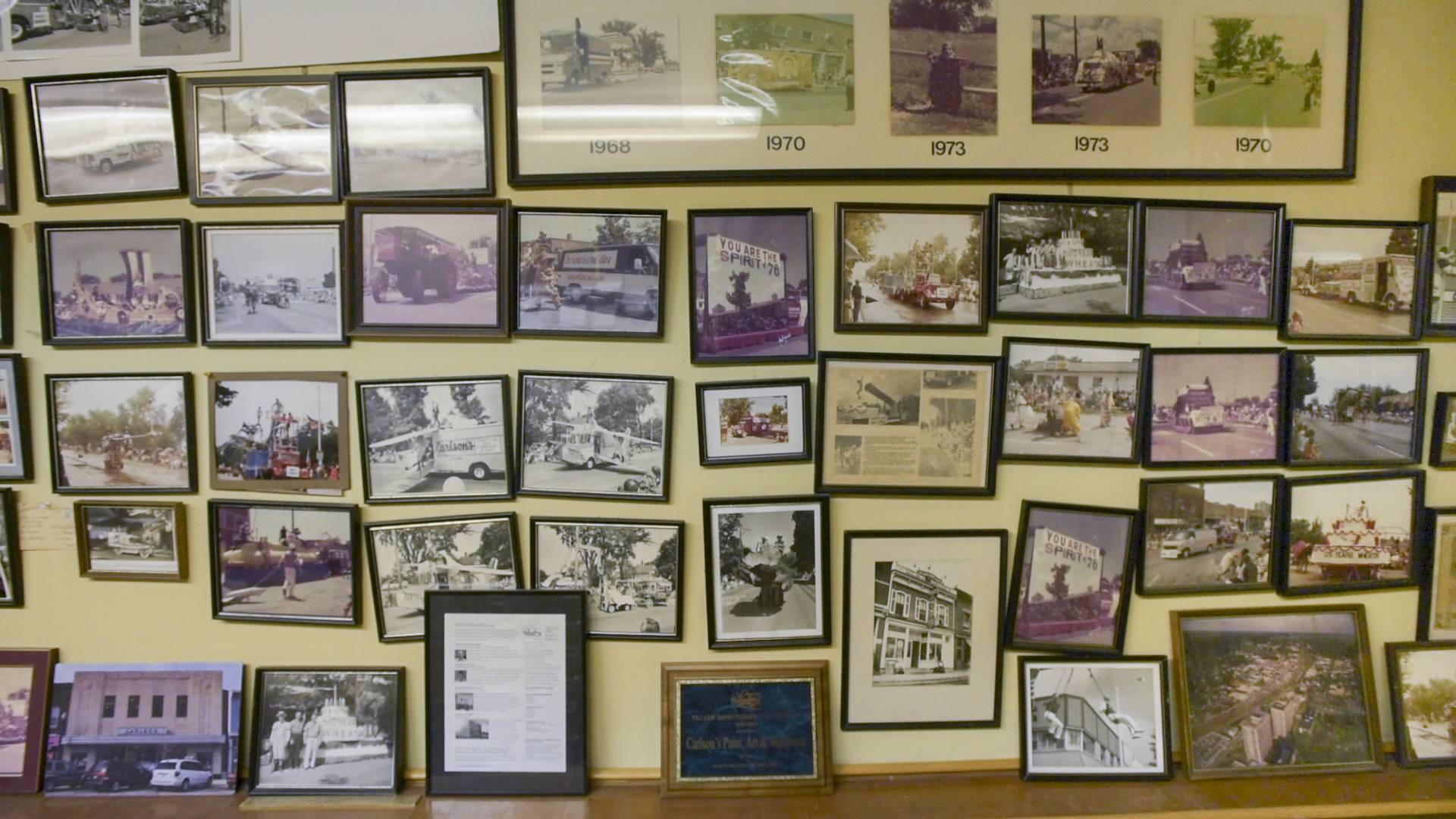 A room above the Carlson Paint, Glass & Art Store in downtown Wheaton is filled with old photographs of the Carlson family's Independence Day parade floats.