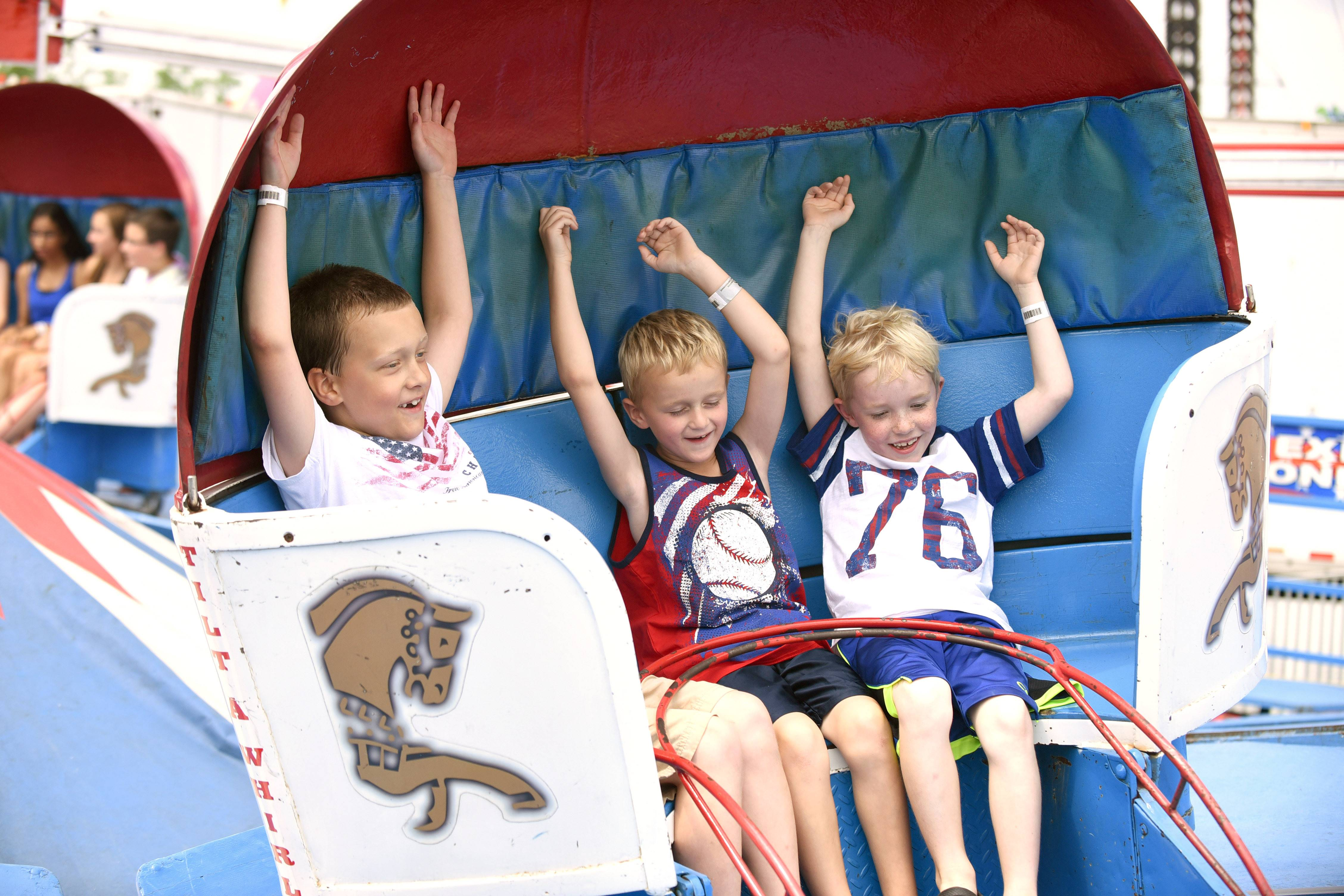 Jack Jerome, 8, from left, Daniel Gunsteen, 7, and Noah Fleck, 7, all of Bartlett, enjoy their spinning car on the Tilt-a-Whirl at Bartlett's 22nd annual Fourth of July festival Friday.