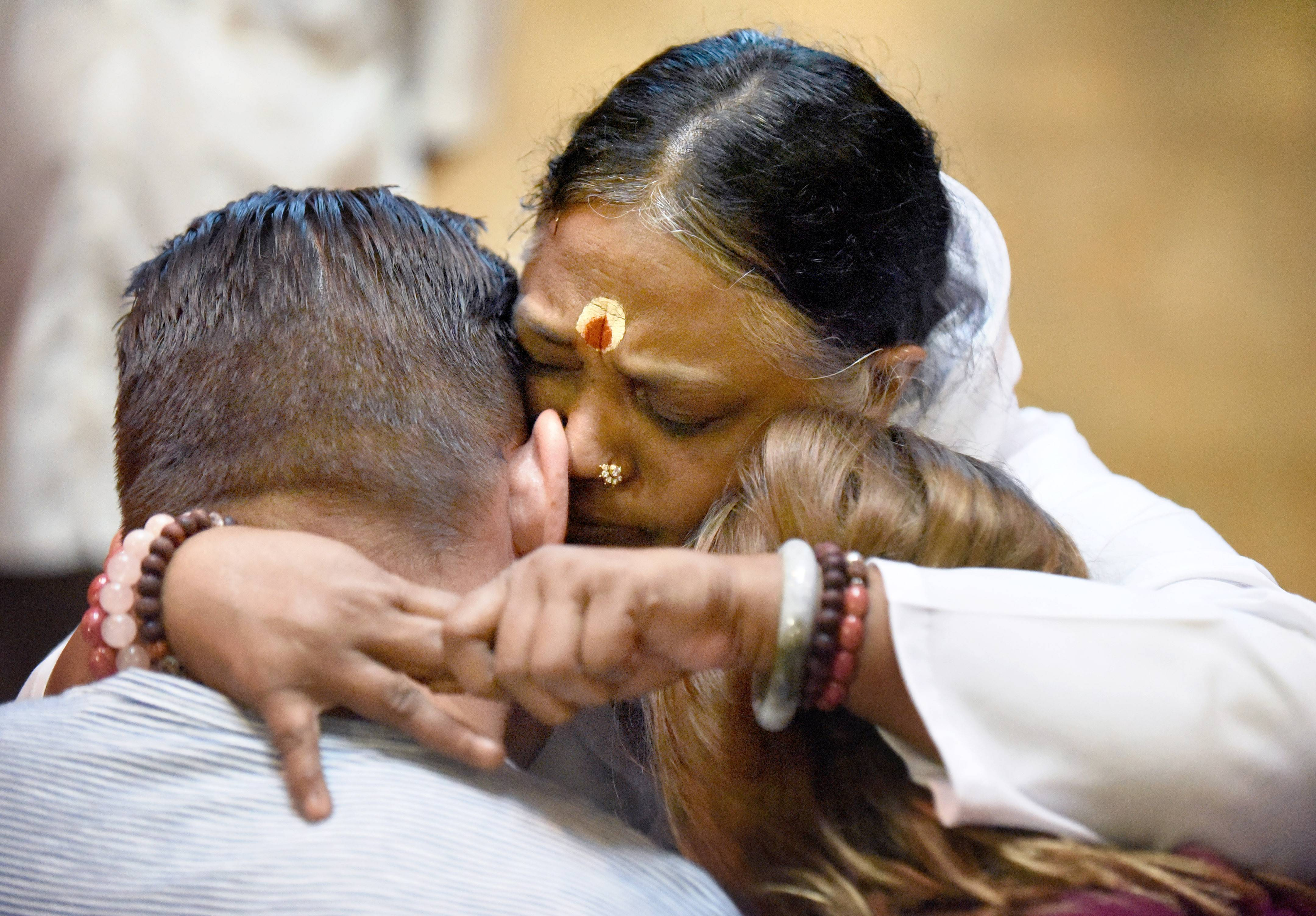 "Amma, a humanitarian and spiritual leader from India who blesses people with hugs, embraces a couple during her Friday morning program at the M.A. Center in Elburn. Amma, whose full name is Mata Amritanandamayi, holds free public programs around the world to offer guidance, share words of wisdom and inspire people ""to get involved in the process of rebuilding a concerned and caring society,"" according to embracingtheworld.org."