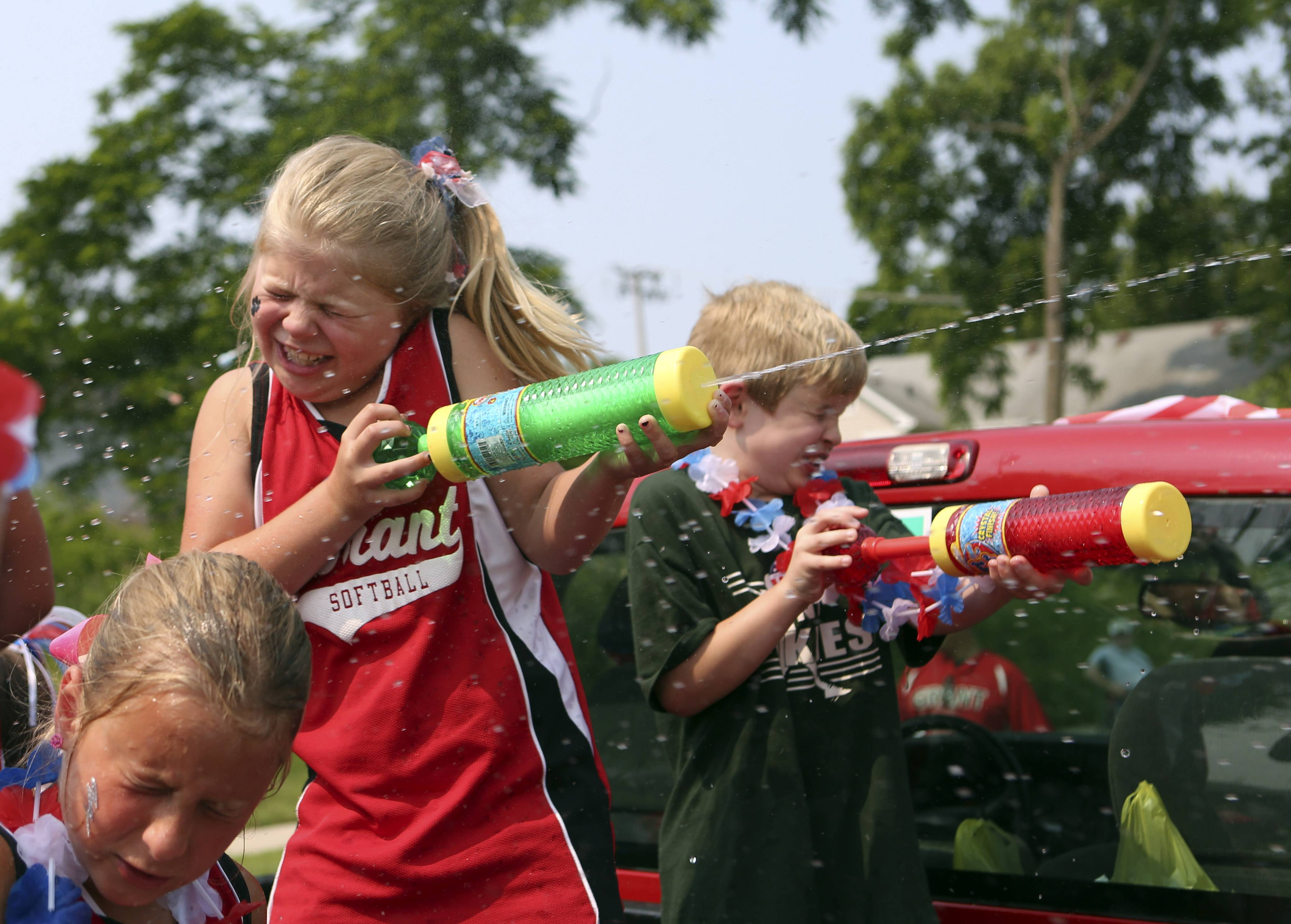Gina-Marie Shearer, center, 8, of Fox Lake, shoots a water gun during the Celebrate Fox Lake Parade on Saturday. The parade started at Grant High School and ended at Towne Center Plaza.