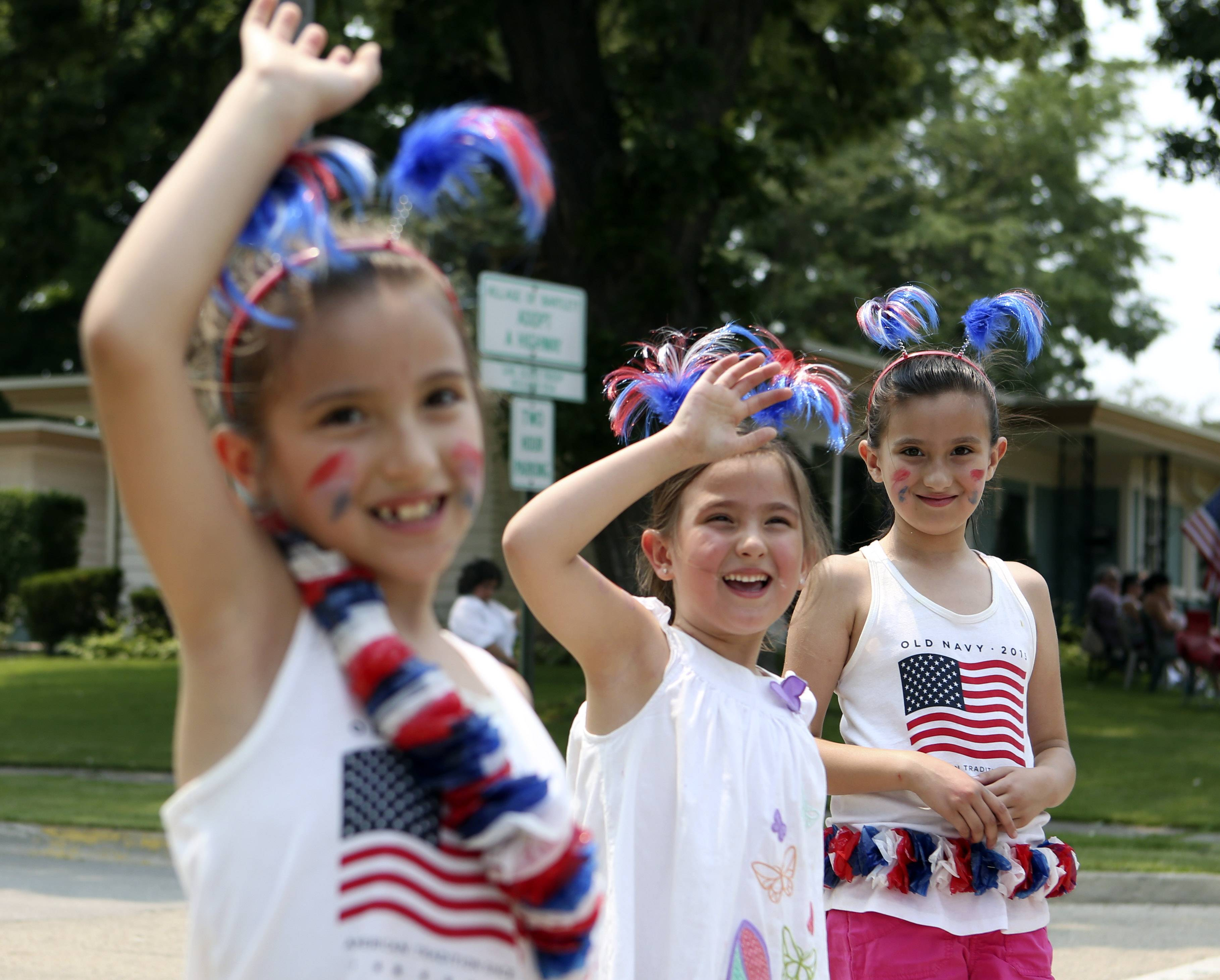 Isabella Garza, center, 5, of Schaumburg, greets parade participants with her sisters Elyssa, left, 7, and Madalyn, 9, during the Bartlett Lions Club Fourth of July Parade on Sunday.