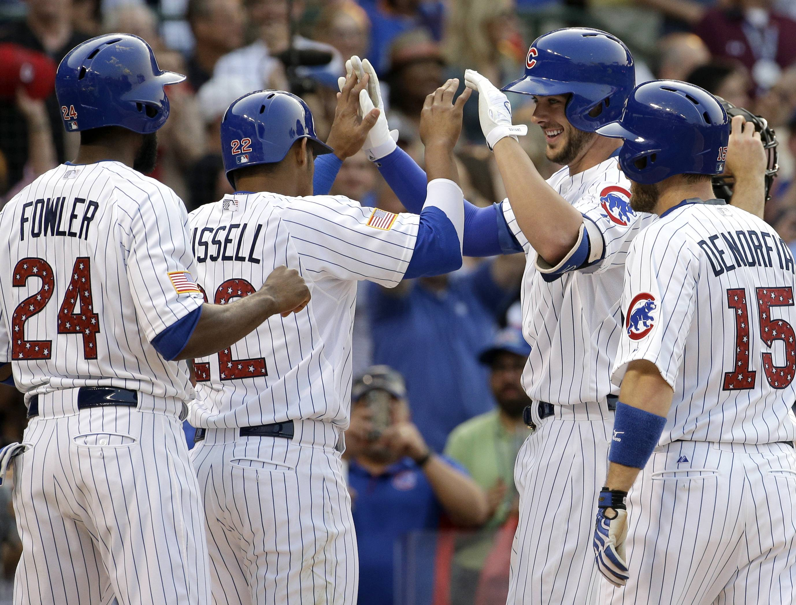 The Cubs' Kris Bryant, second from right, celebrates with teammates Addison Russell (22), Dexter Fowler (24) and Chris Denorfia (15) after hitting a grand slam during the second inning Saturday night against the Miami Marlins at Wrigley Field.