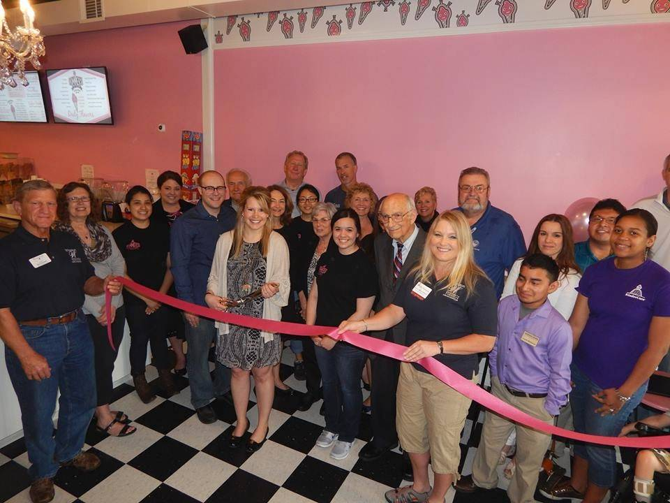 Kim Elam, holding the scissors, cuts the ribbon on her second ice cream store called Kimmer's Ice Cream in Wheaton.