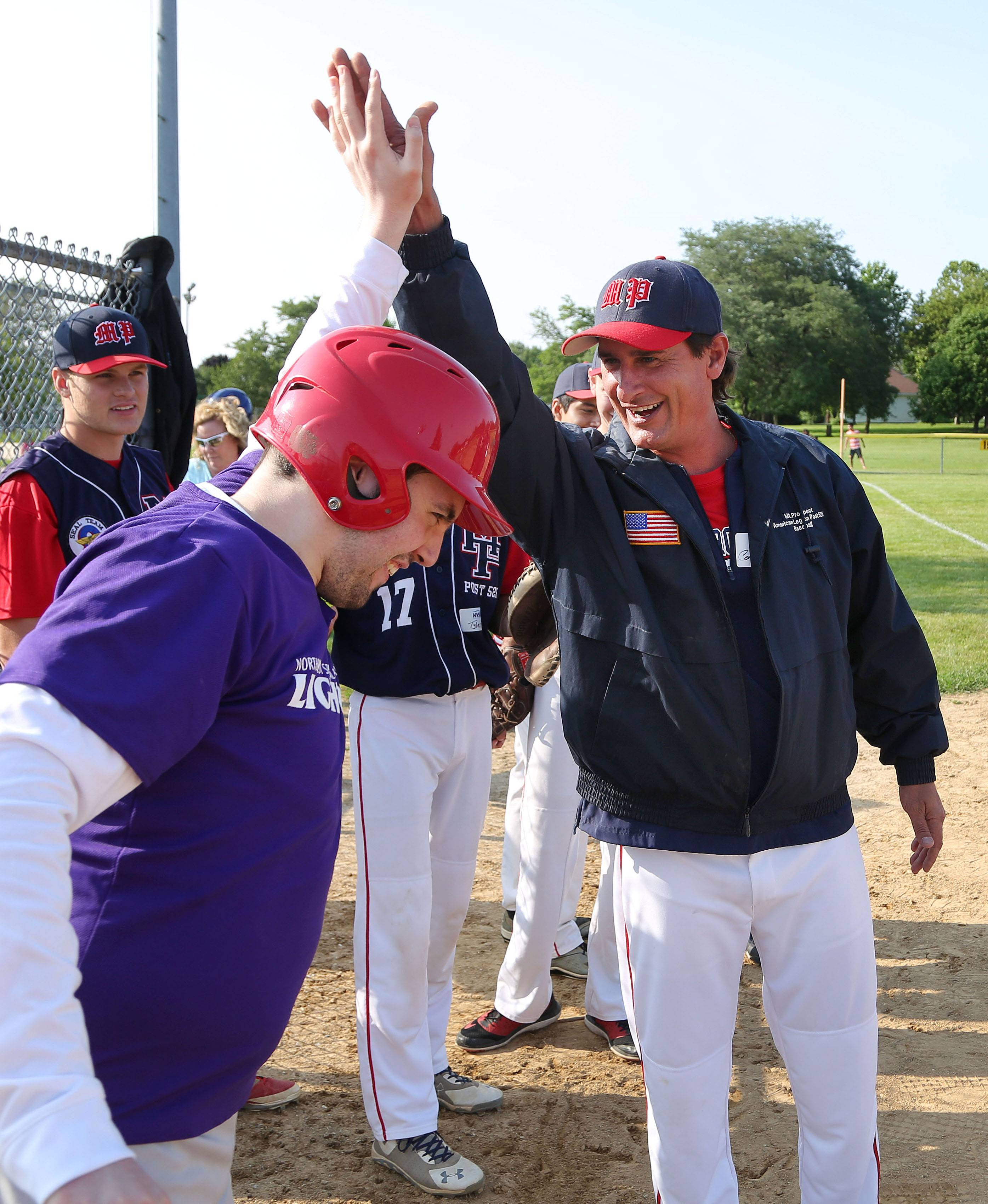 Gus Gilbertson, left, high-fives American Legion assistant coach Jim Haffey as 25 athletes from Northwest Special Recreation Association were paired up with high school players from the American Legion Mount Prospect Bulldogs Post 525 baseball team Tuesday during the 2015 Summer Classic at Friendship Park Conservatory in Des Plaines.
