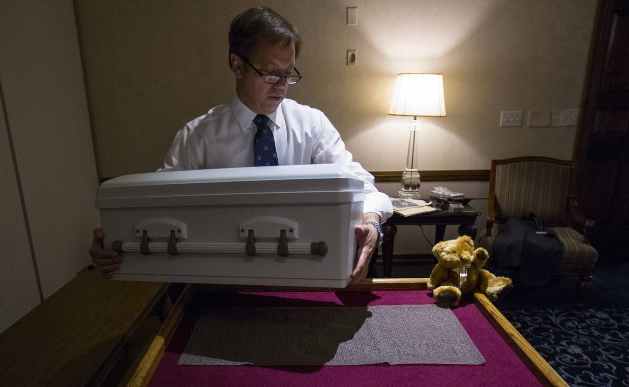 Funeral Director John Glueckert of Glueckert Funeral Home in Arlington Heights lifts the casket containing the remains of an abandoned newborn baby onto a table in preparation for funeral and burial services.