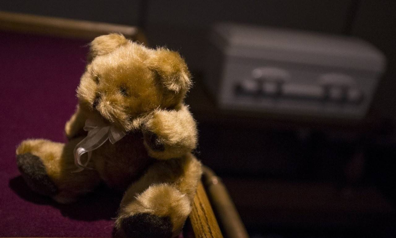 A teddy bear sits on a table next to the casket containing the remains of an abandoned newborn baby in preparation for funeral and burial services at Glueckert Funeral Home in Arlington Heights.